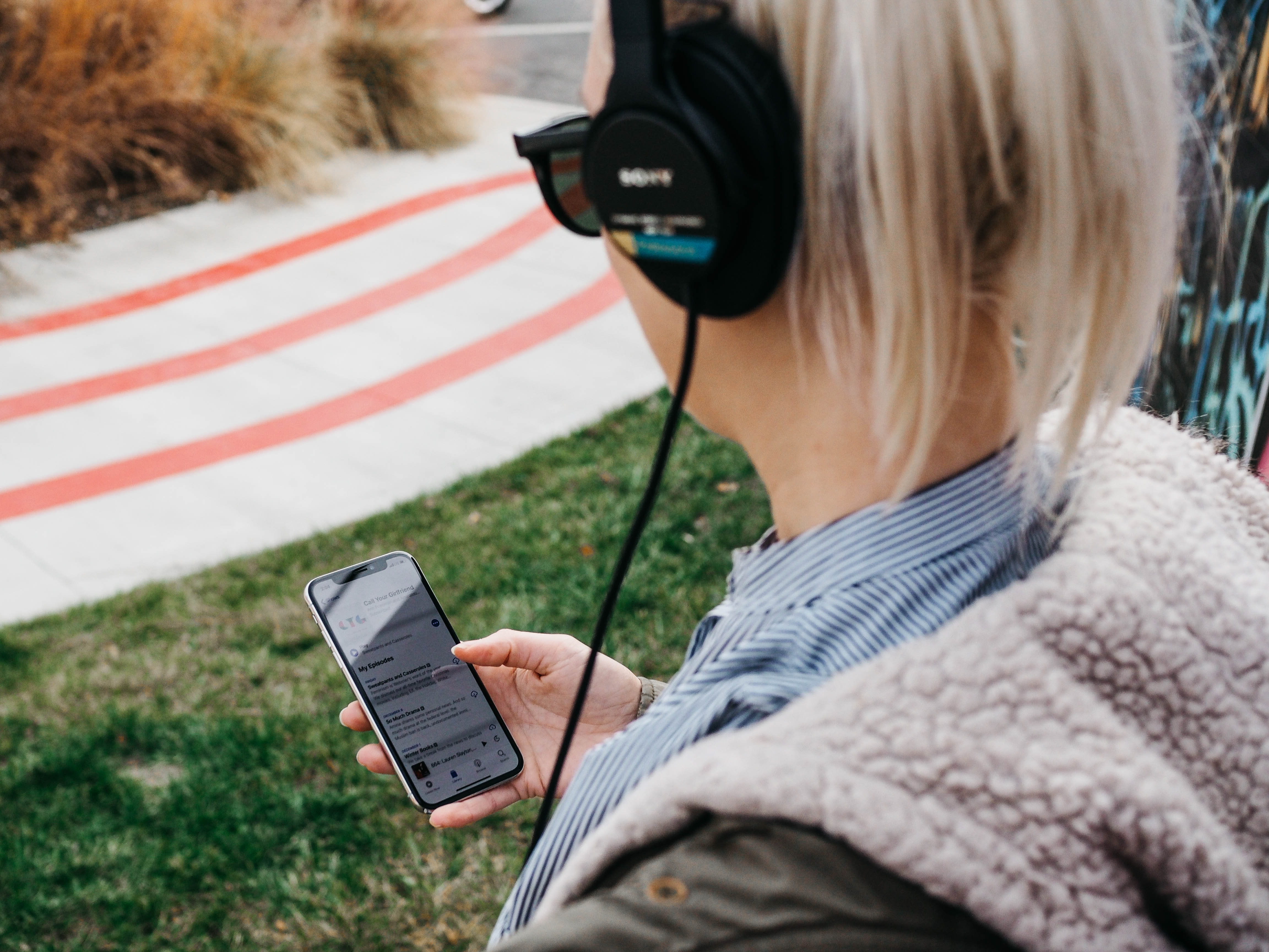 woman wearing black headphones while holding black Android smartphone