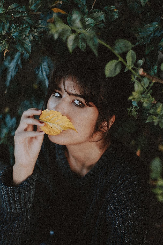 woman smelling brown leaf