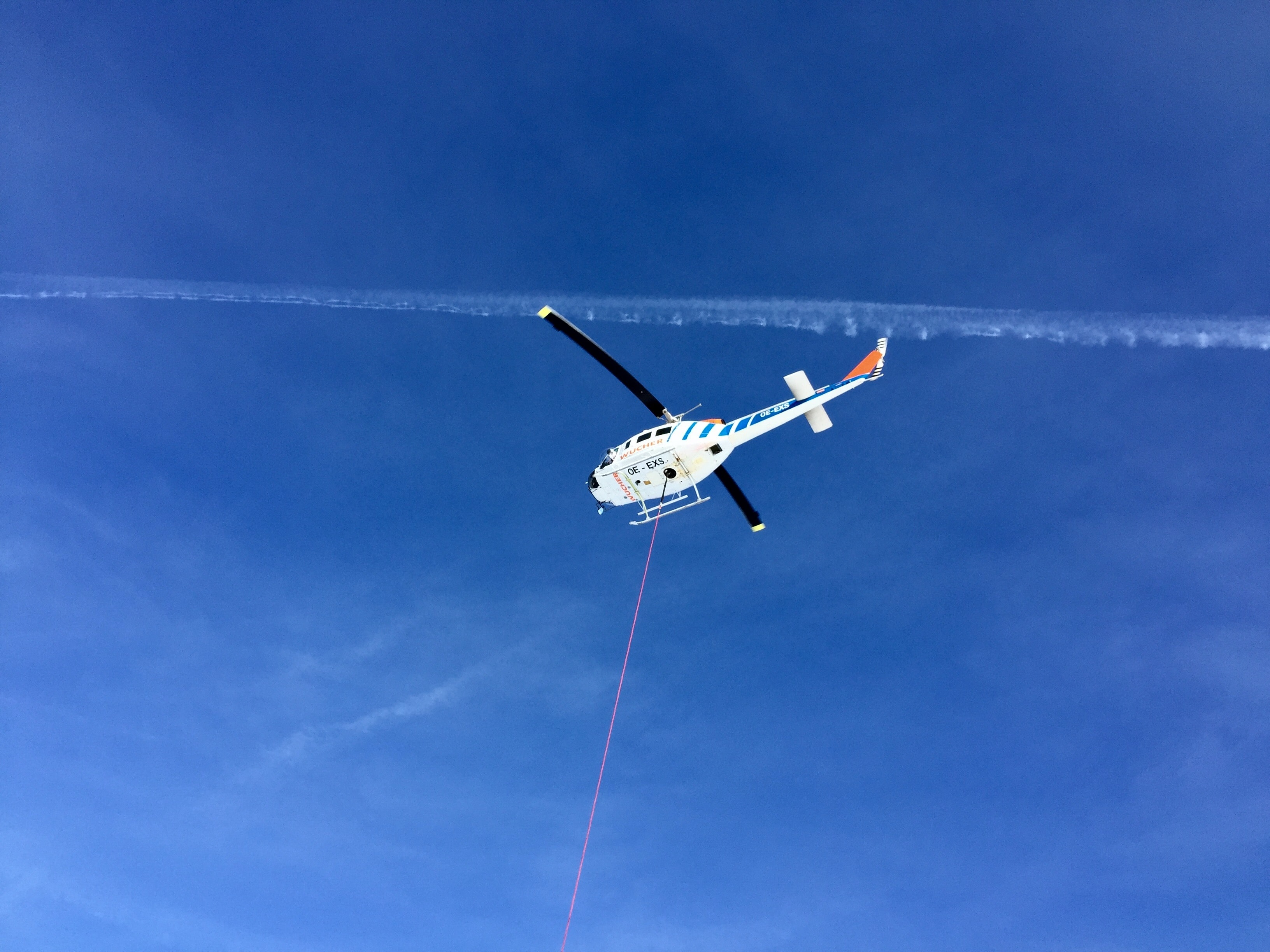 worm's-eye view of helicopter under cloudy sky