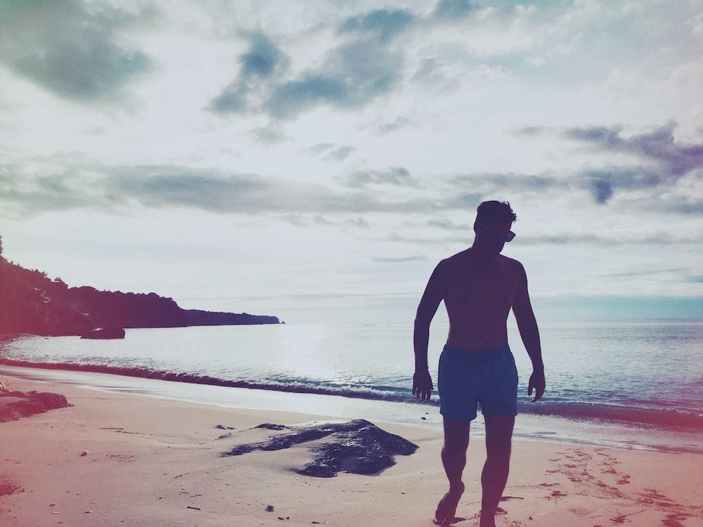 man walking on brown sand under gray sky during daytime