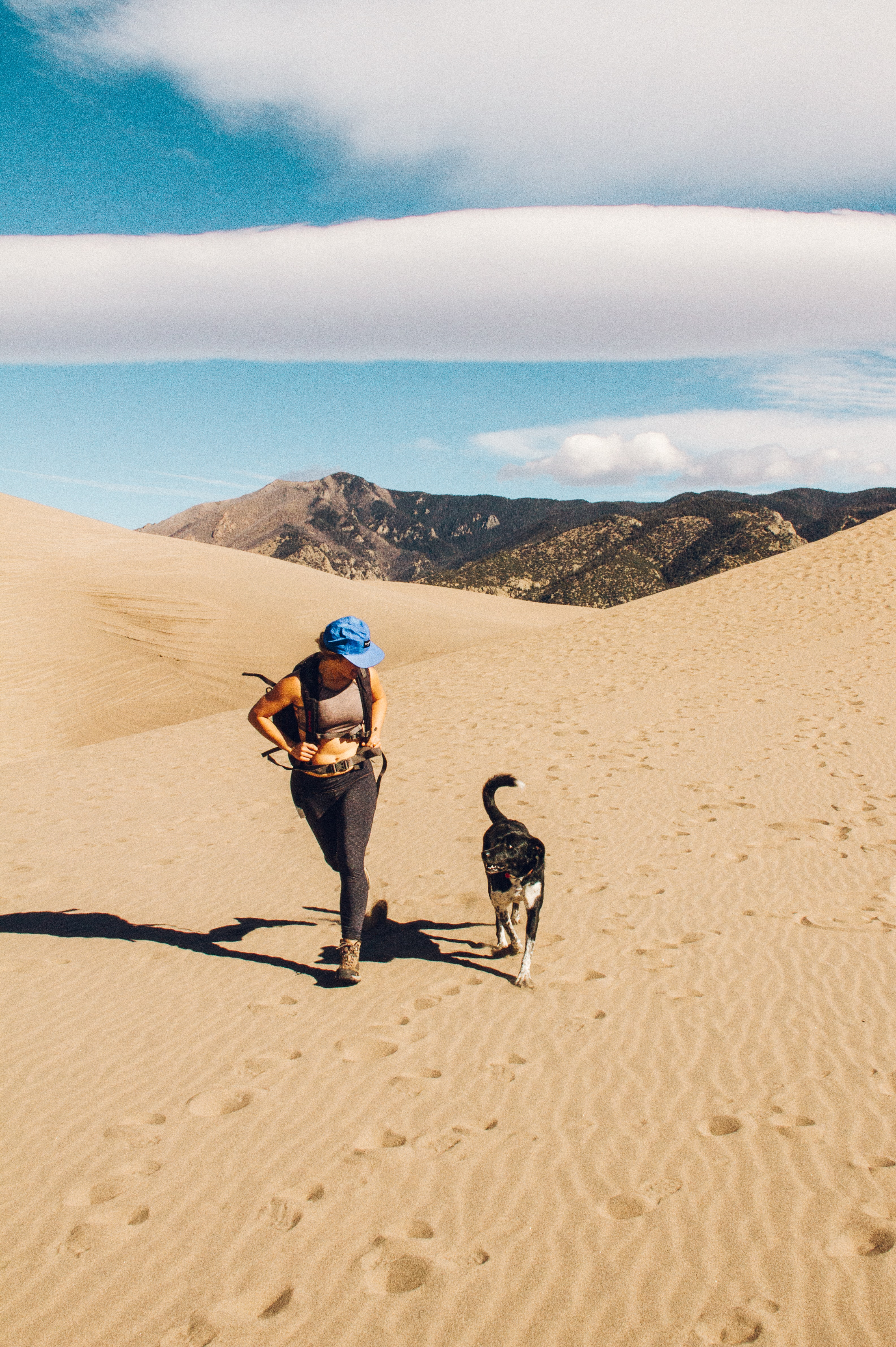 woman and dog walking on desert