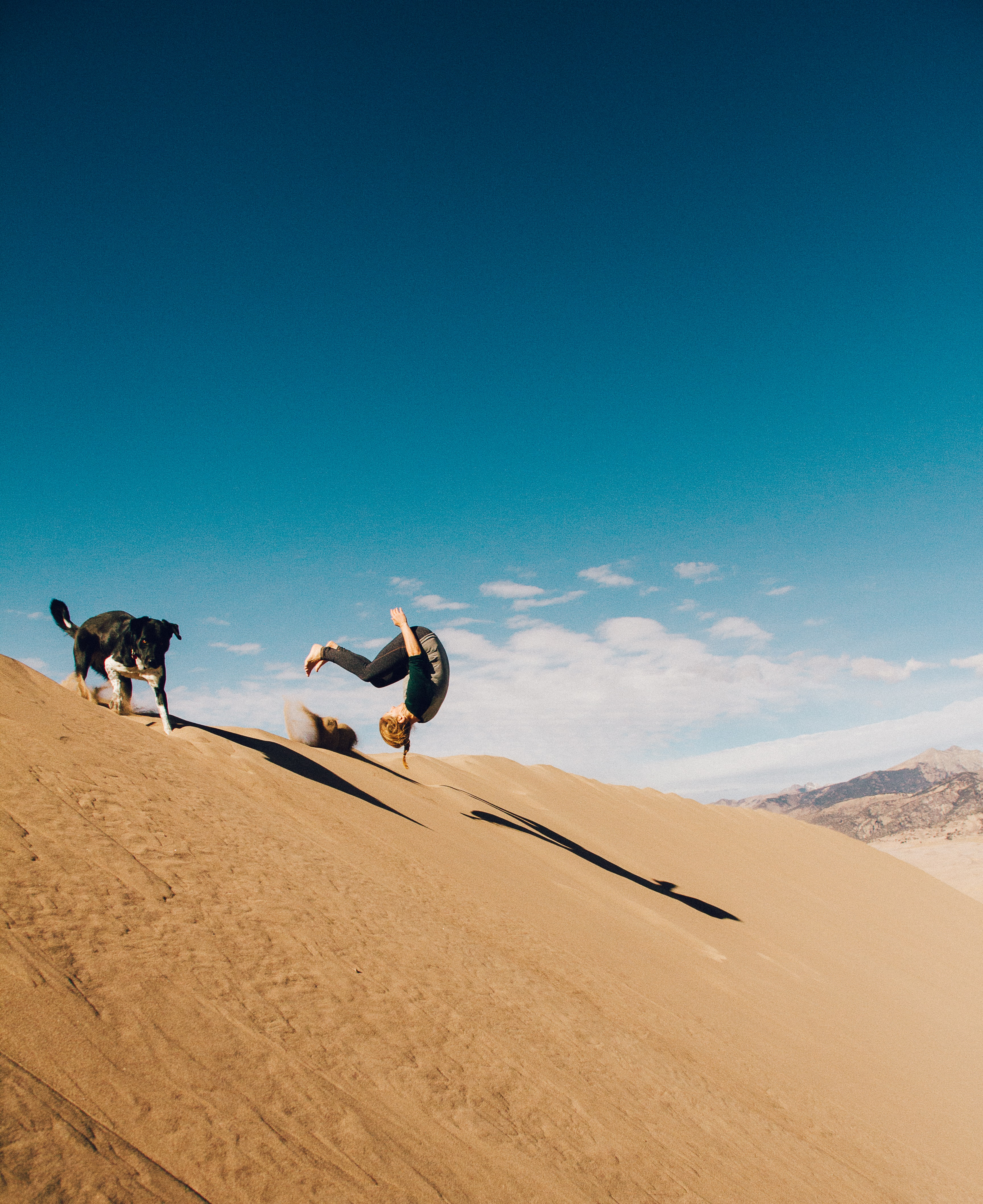 person doing back-flip in the desert dune