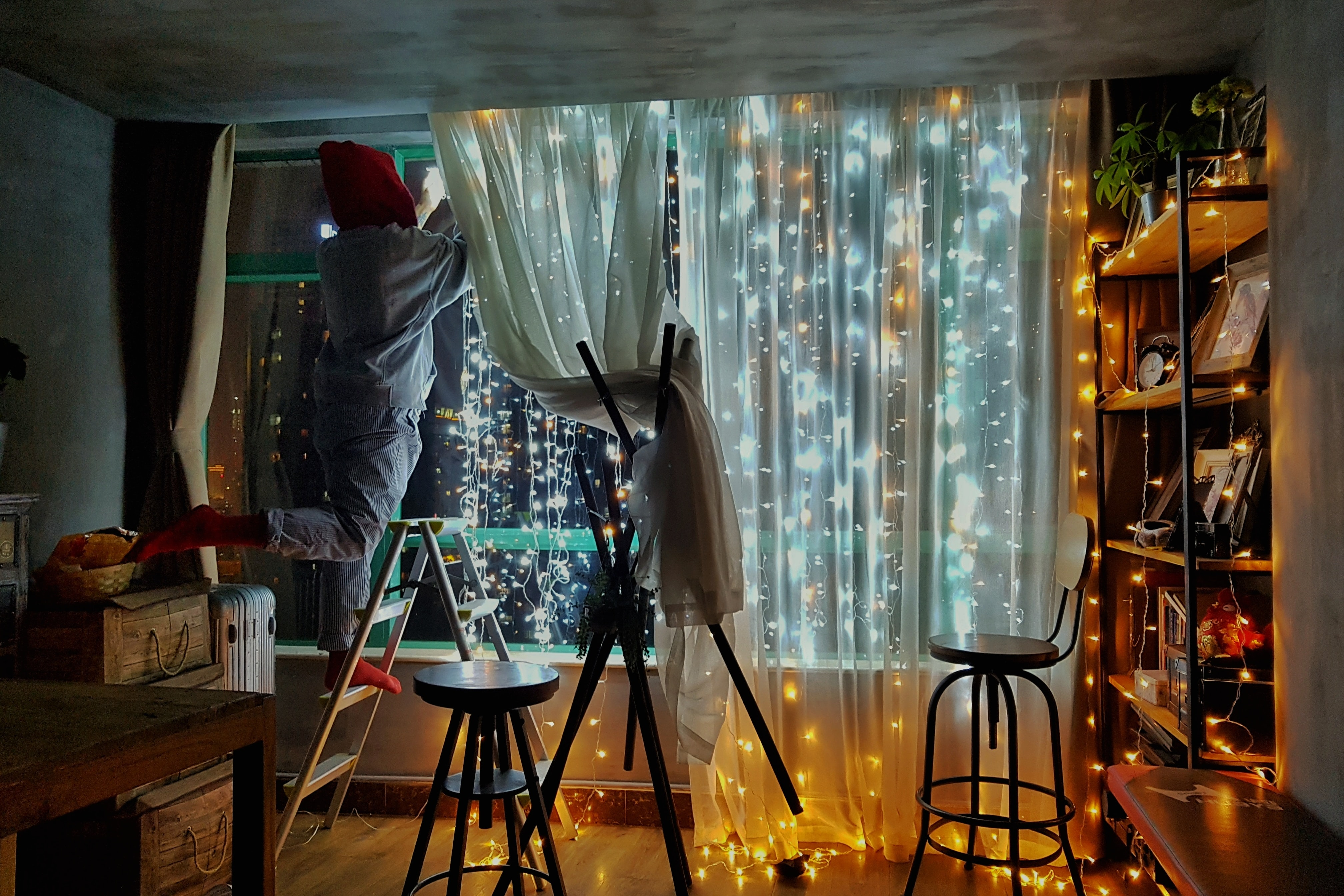 person standing on step ladder in front of string lights