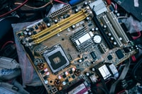 closeup photo of brown, yellow, and black Asus motherboard