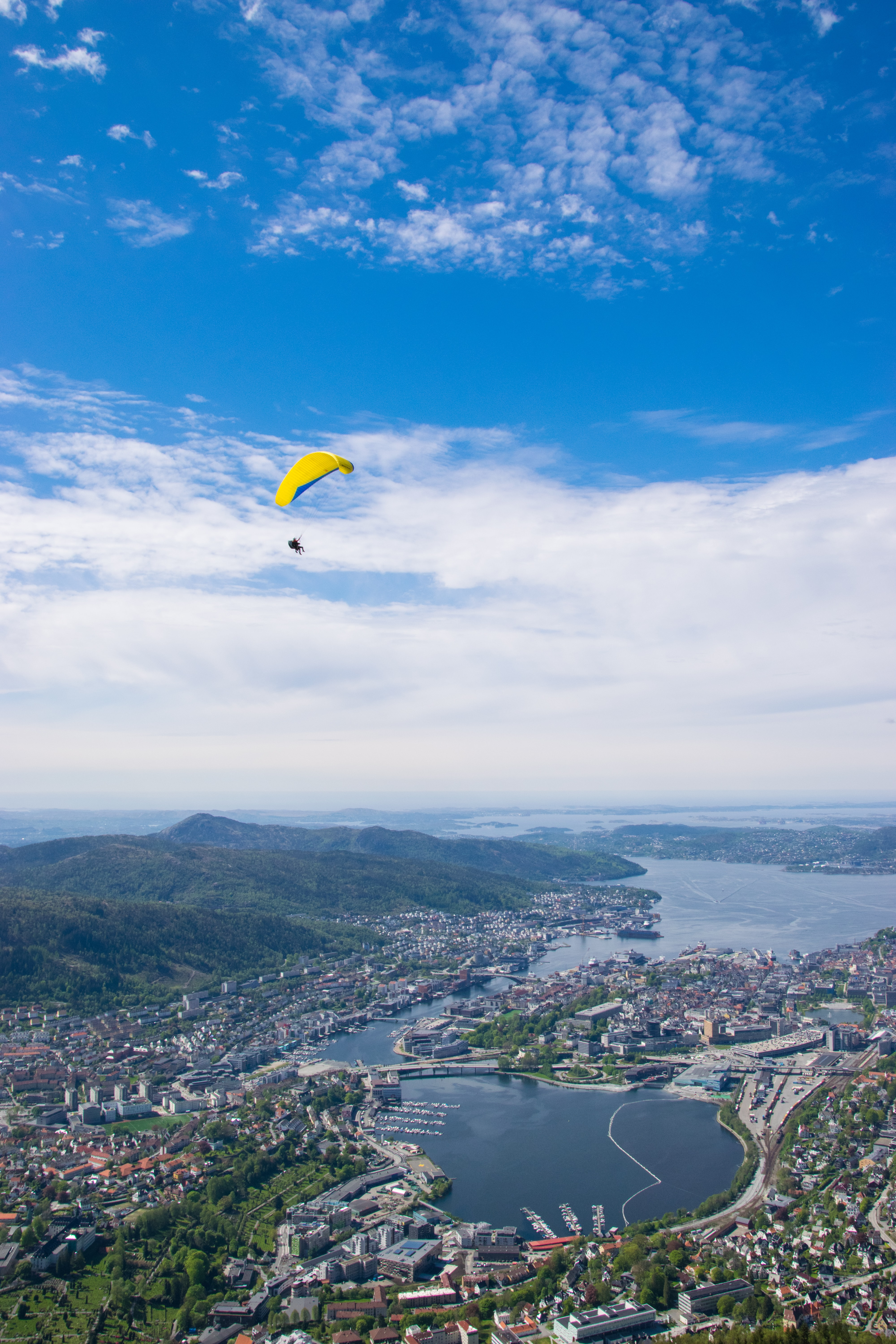 person paragliding over city