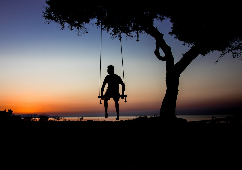 silhouette photo of man on swing beside tree