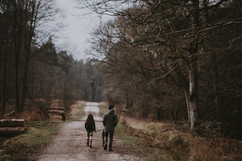 man and child walking on road surrounded by trees