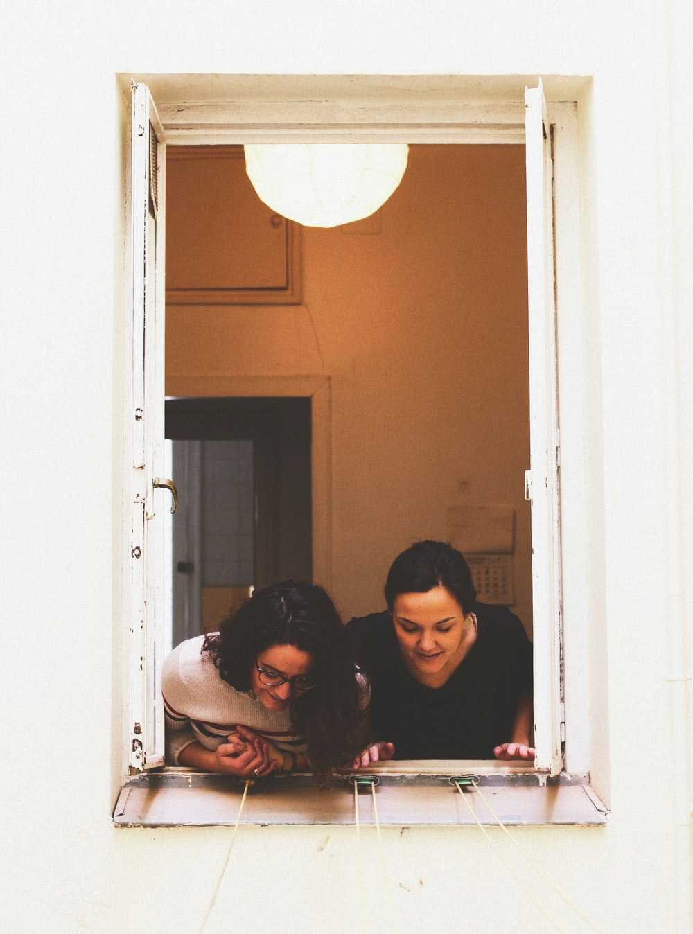two woman looking through window