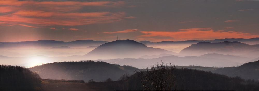 silhouette photo of mountains surrounded by fogs