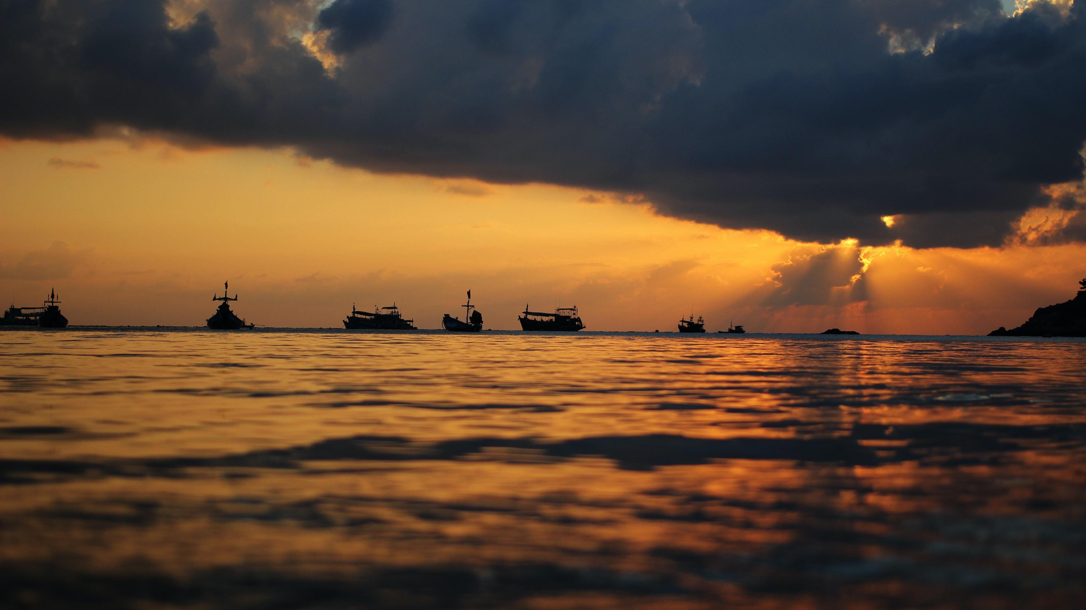 landscape photography of group of ships under golden hour