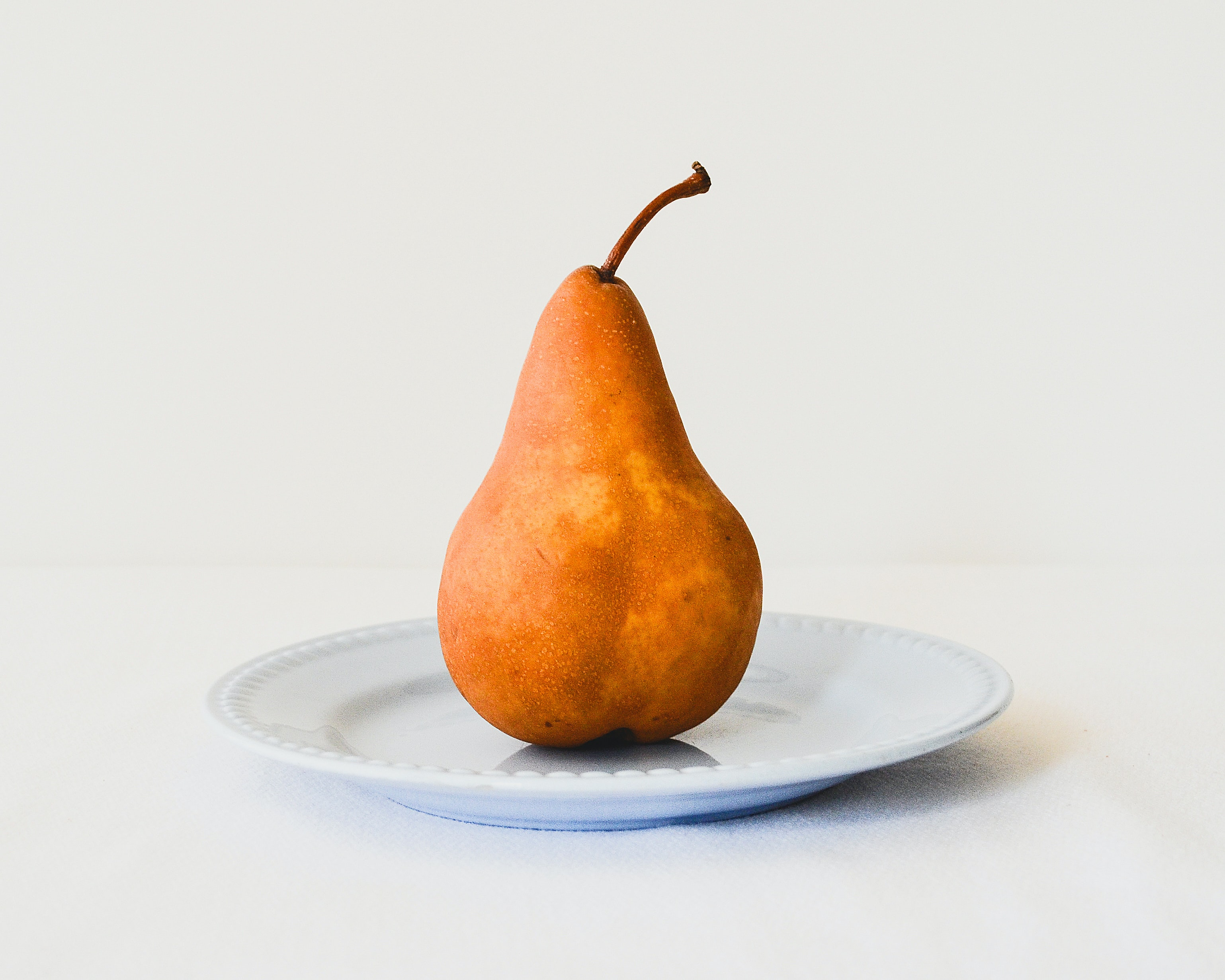 orange pear on white ceramic plate
