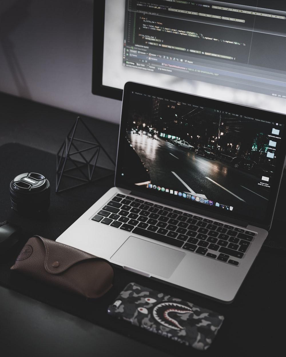 liguei o MacBook Pro na frente do monitor preto de tela plana do computador