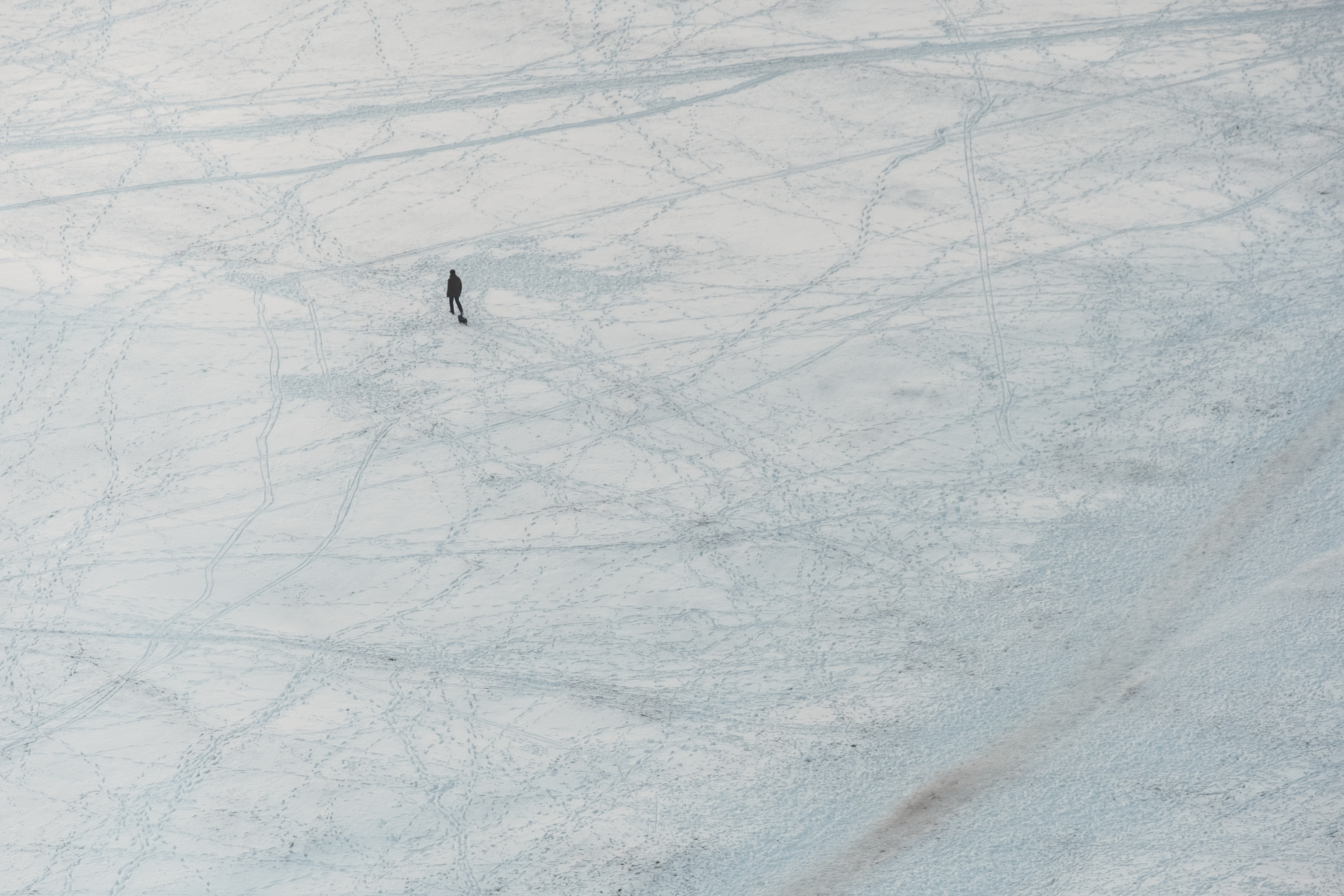 aerial view of person walking on snow covered ground