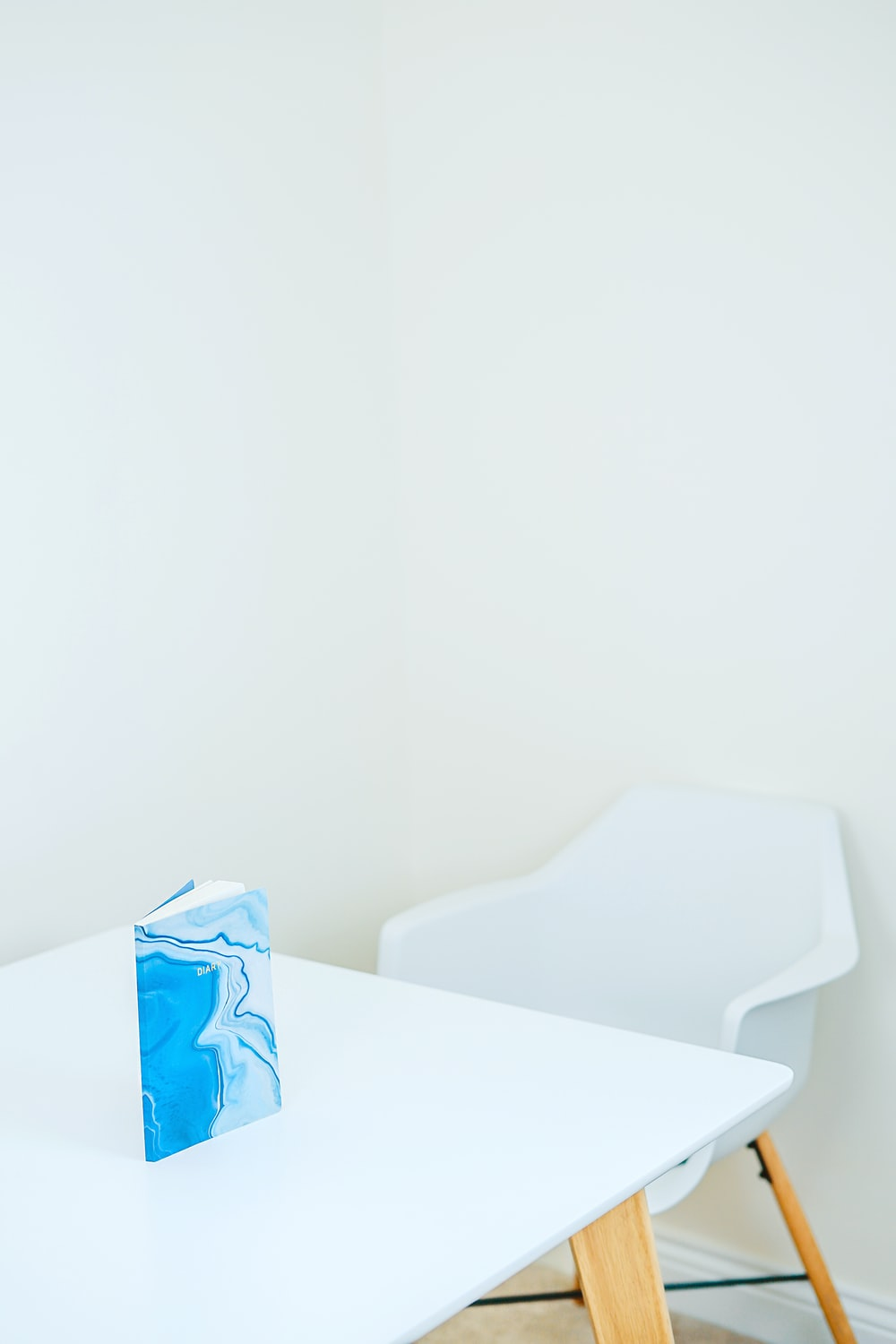 blue and white hardbound book on white wooden table
