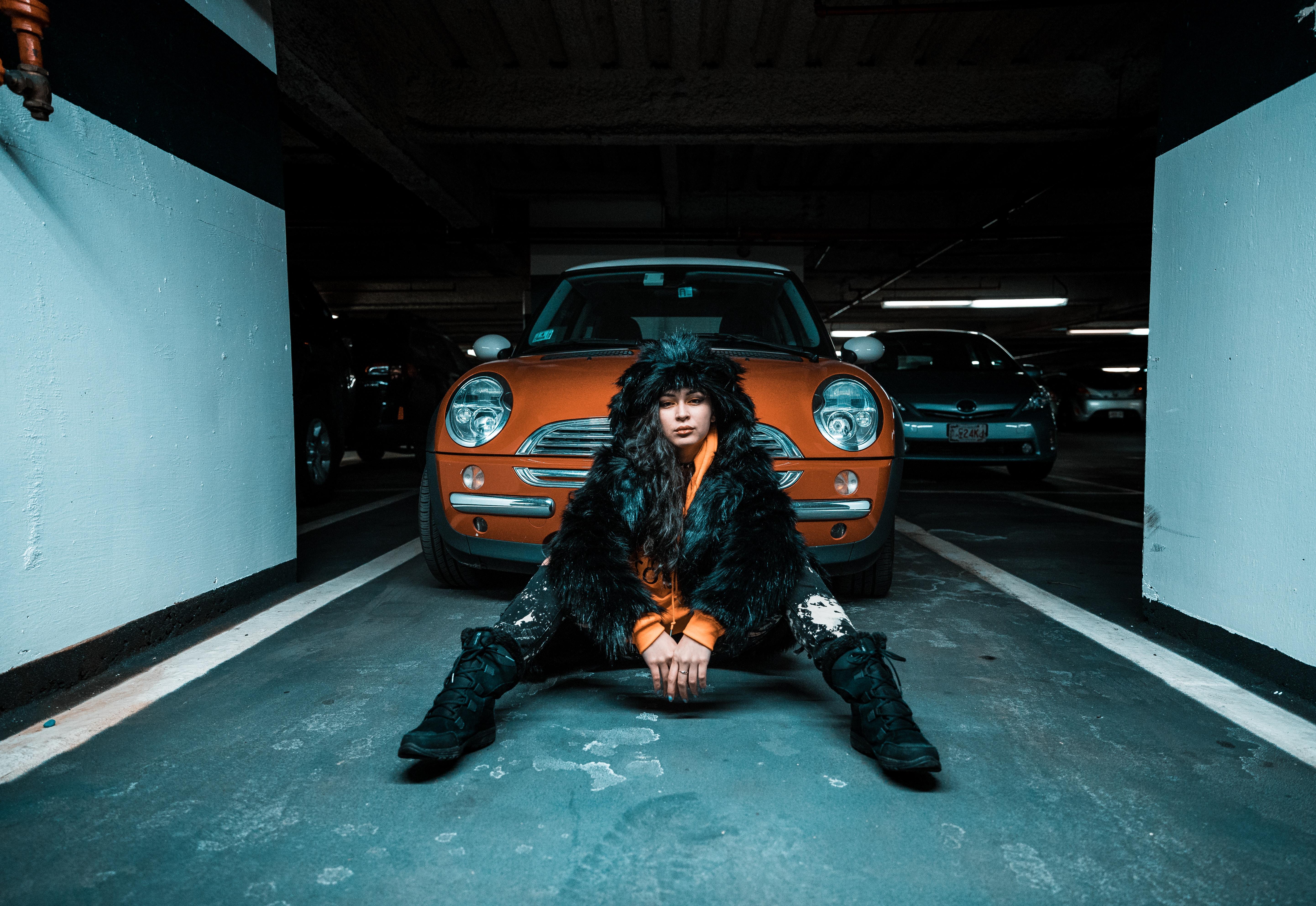 woman sitting on pavement near car