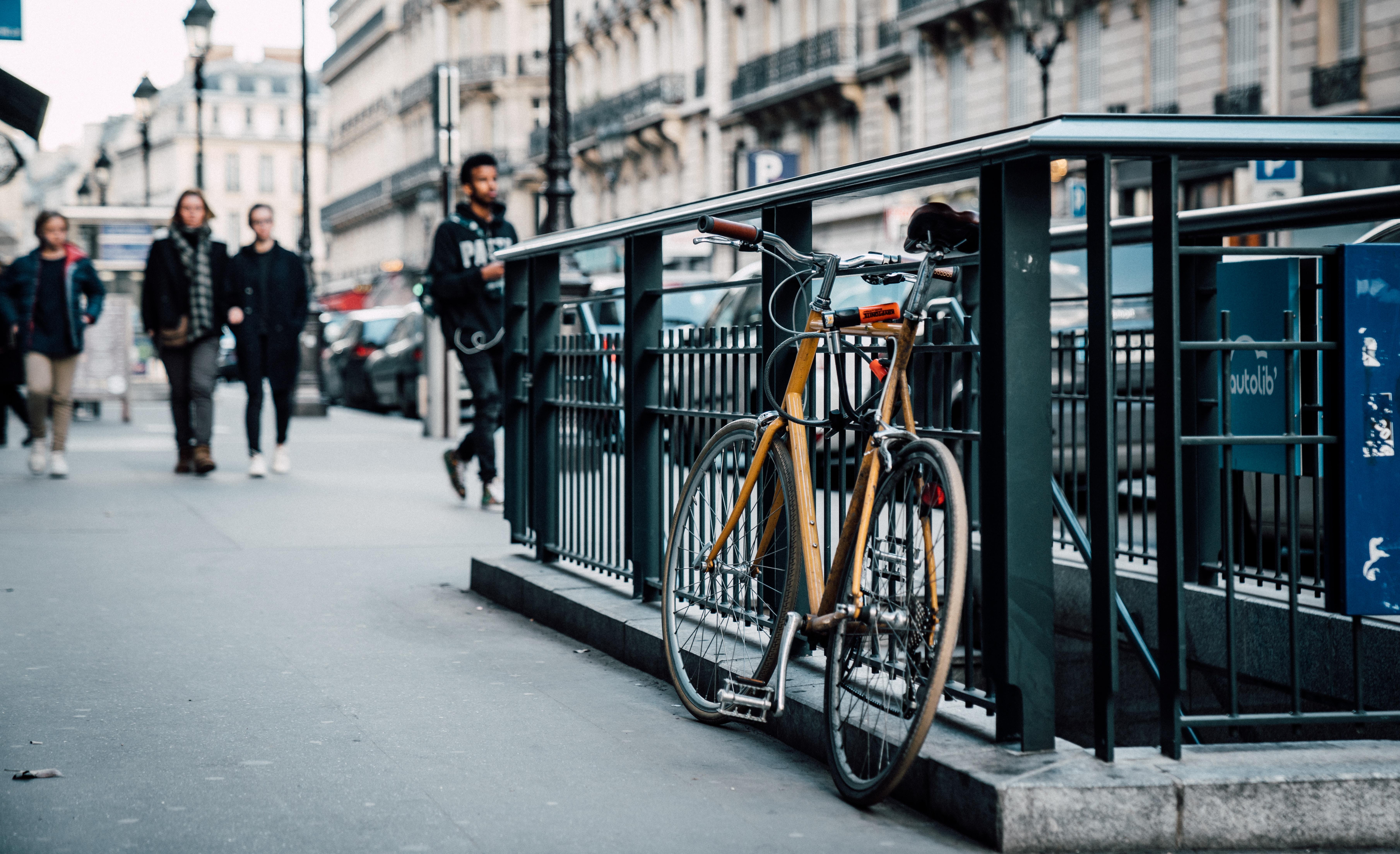 parked orange bicycle on subway railings