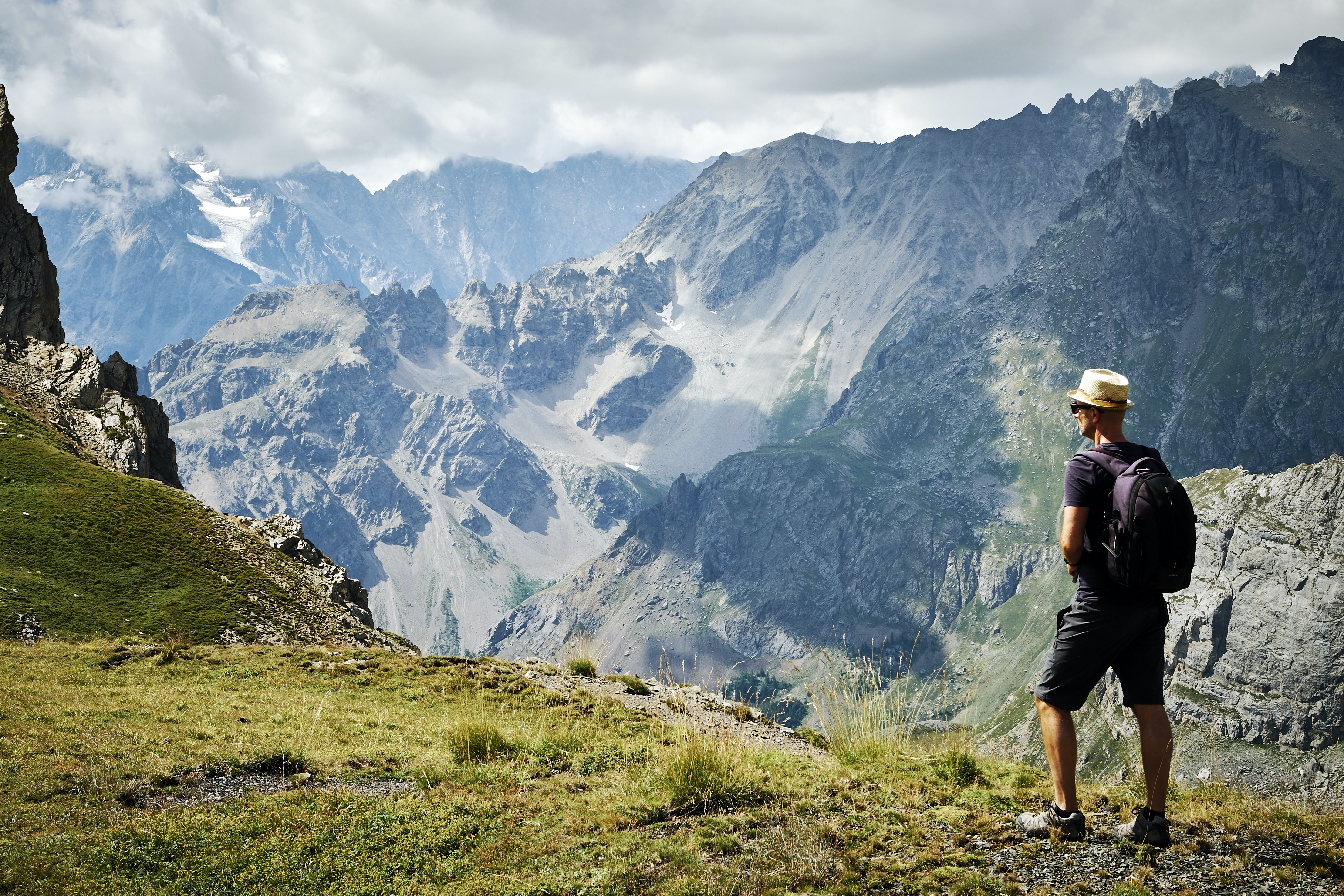 photo of man standing near mountains