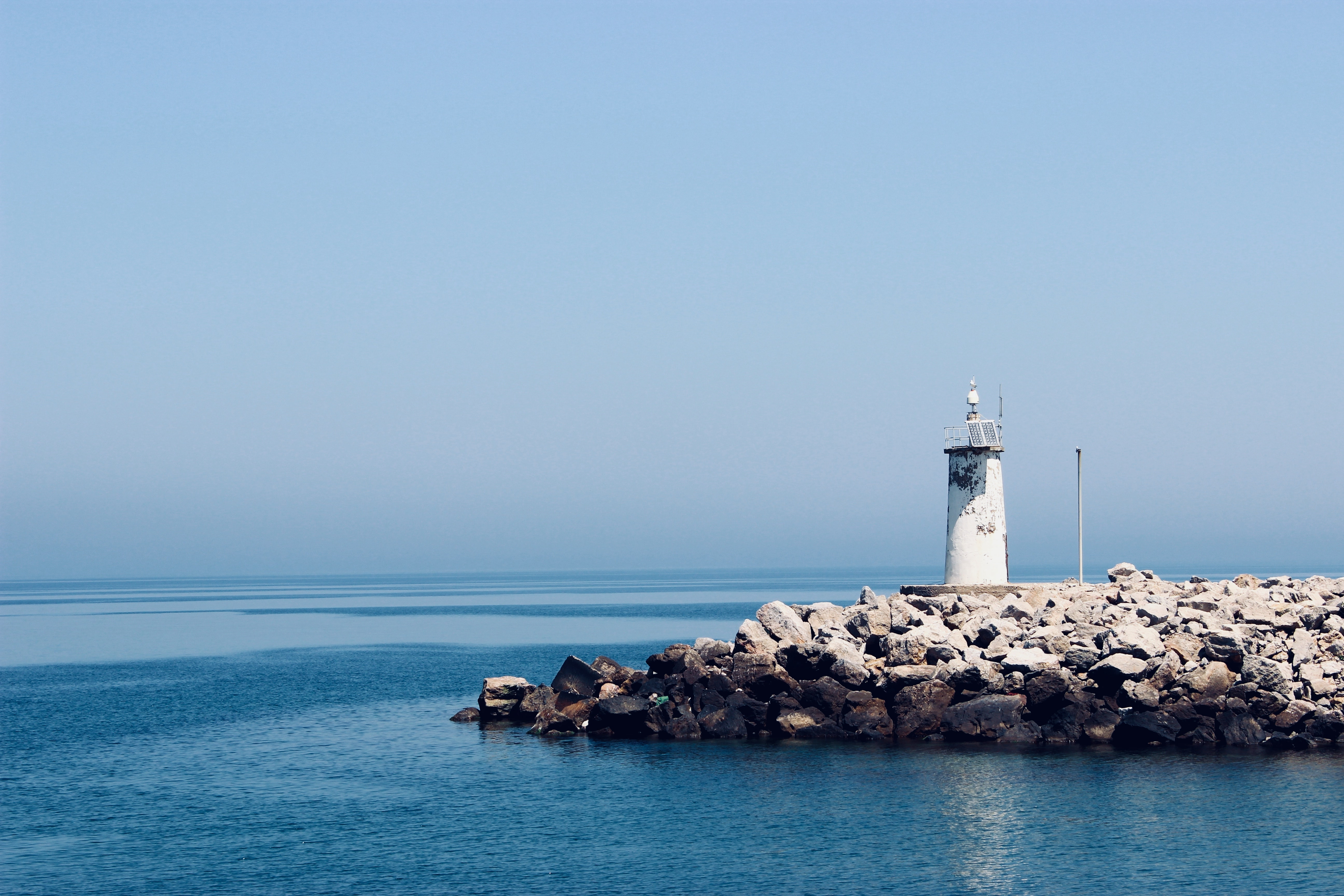 photograph of white lighthouse on rocks