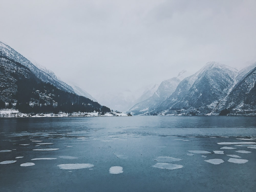 body of water surrounded by snowy mountain