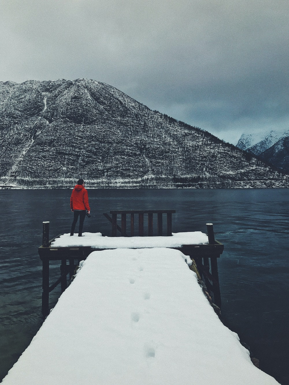 person standing on dock covered with snow looking at mountain across body of water