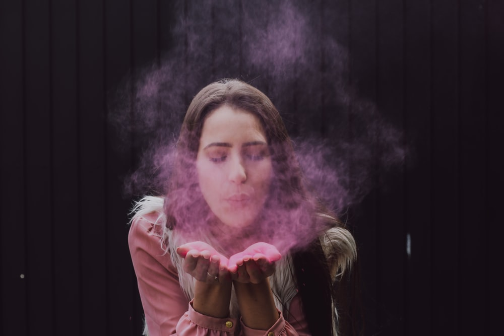 woman blowing smoke on her both hands