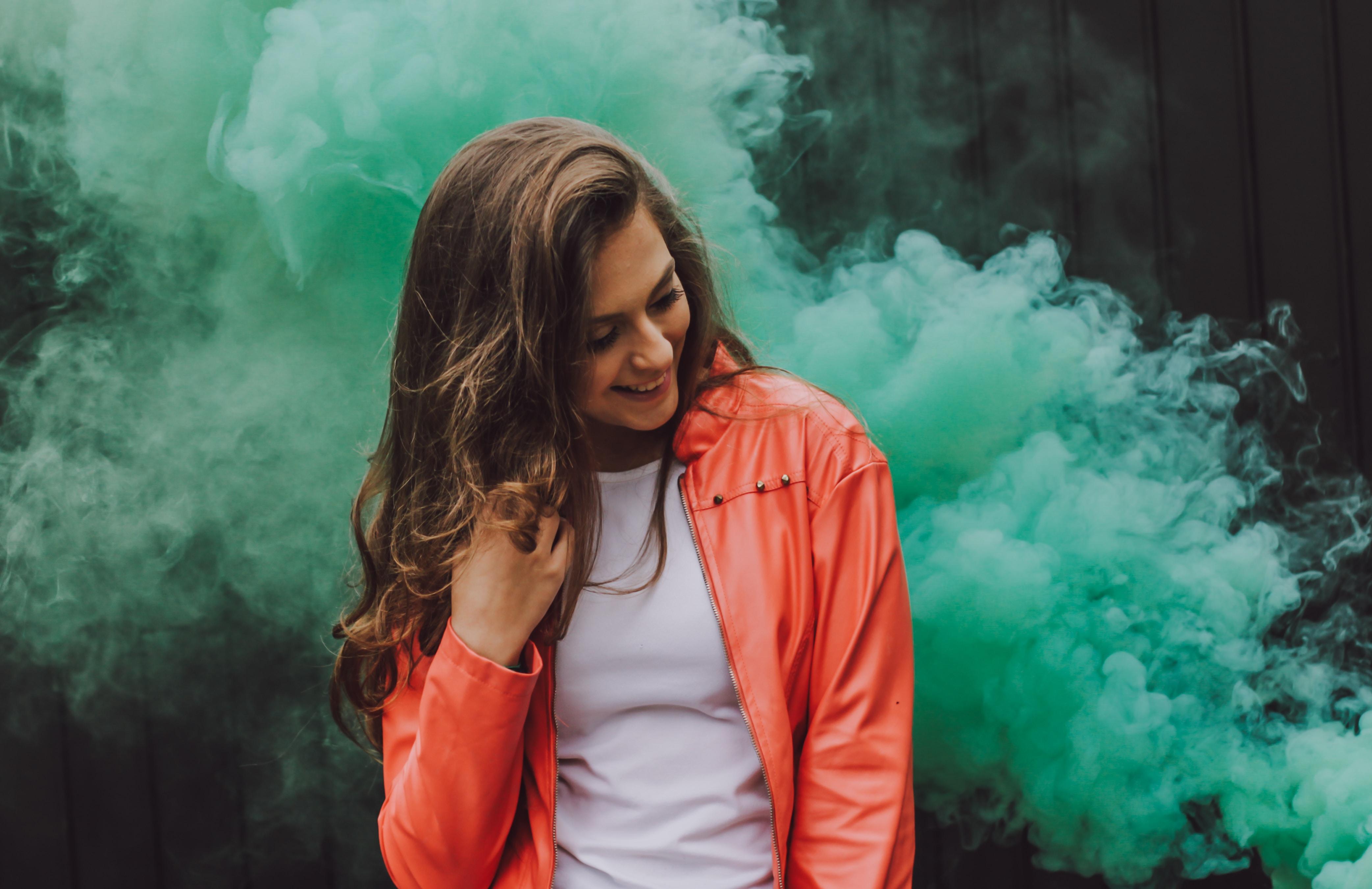 woman wearing orange leather jacket surrounded by green smoke