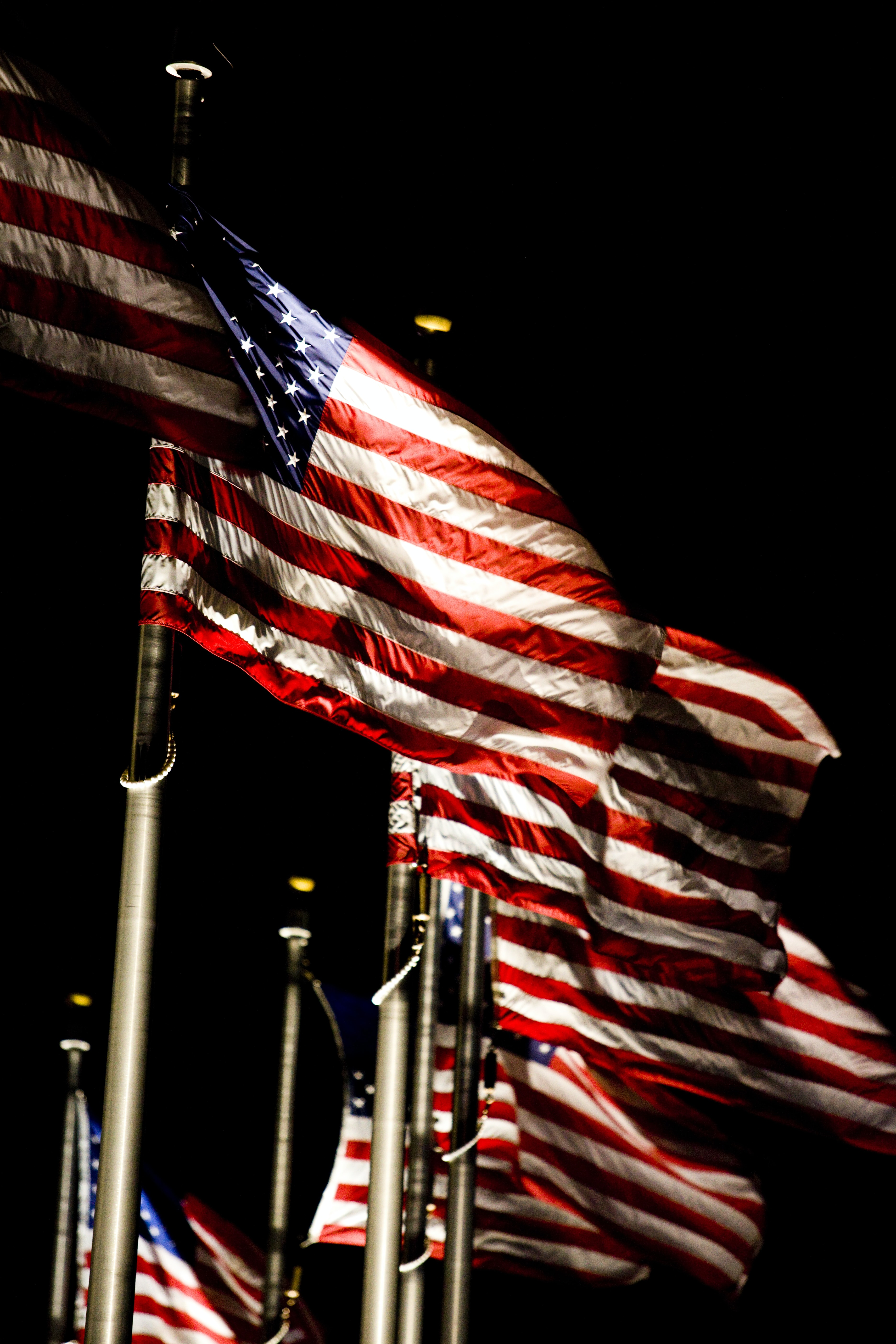 flags of the United States of America on flag poles under dark sky