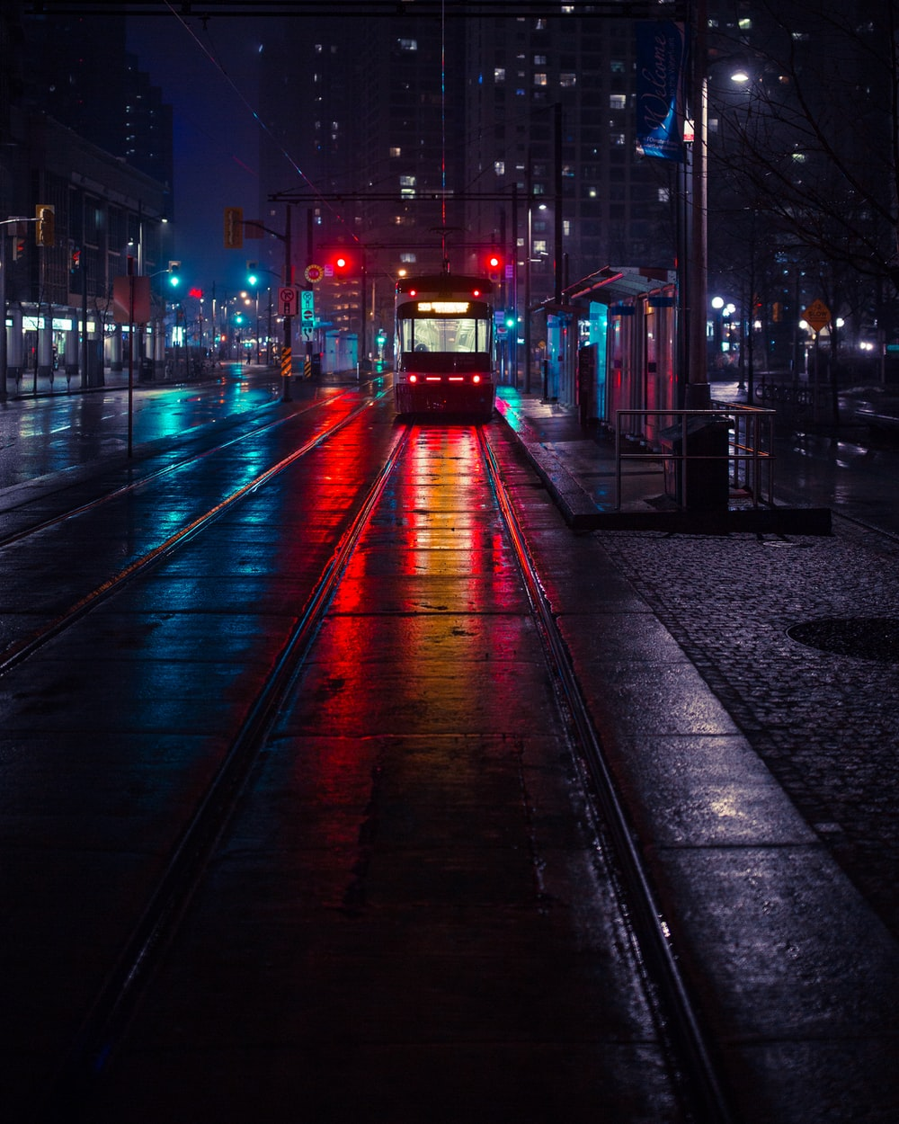 photo of tram beside waiting station during nighttime
