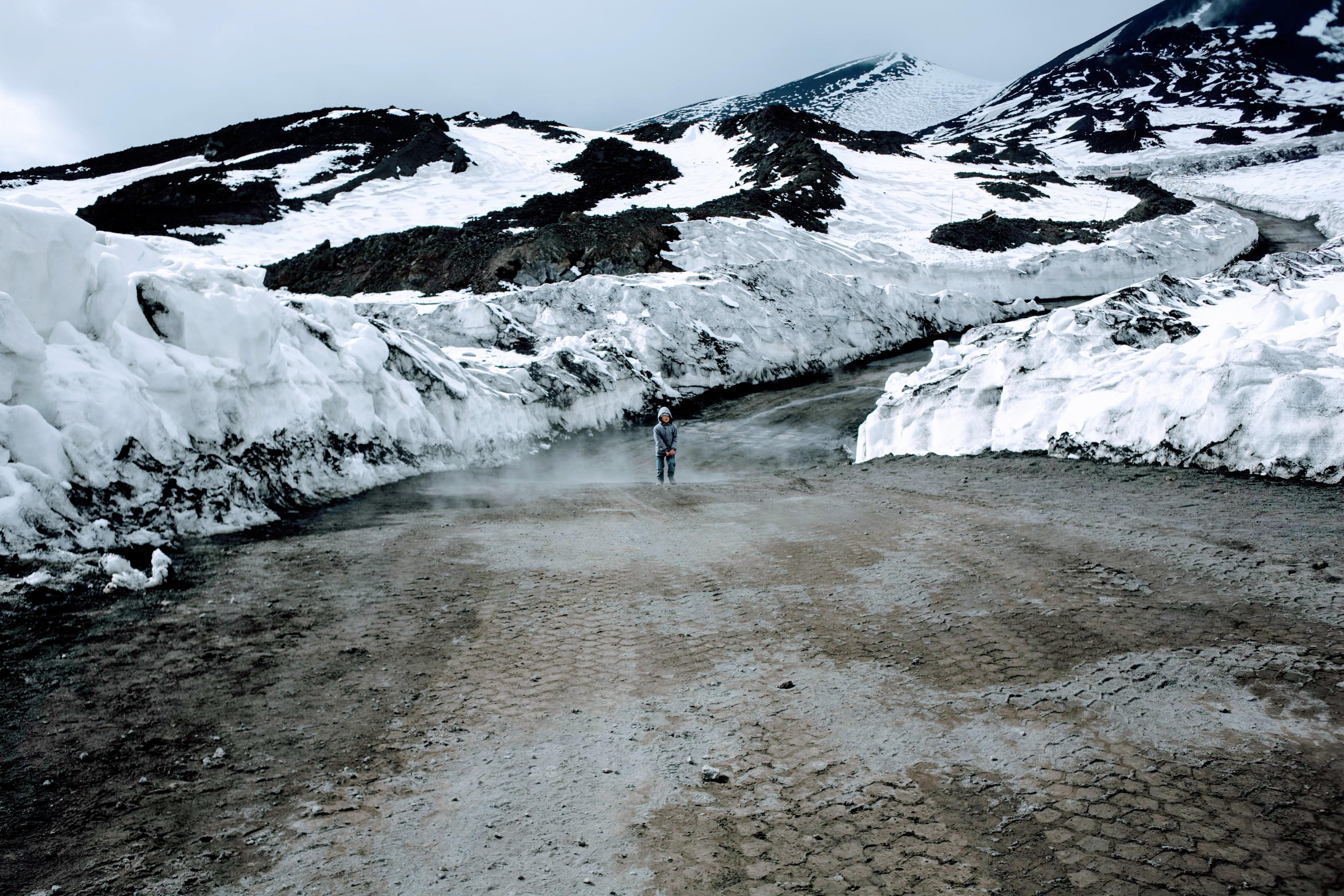 person standing near snow caps mountain