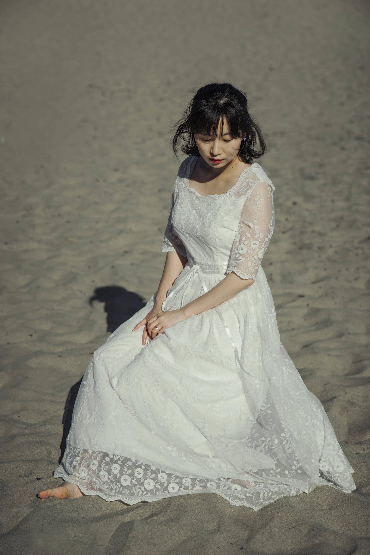woman sitting on gray sand