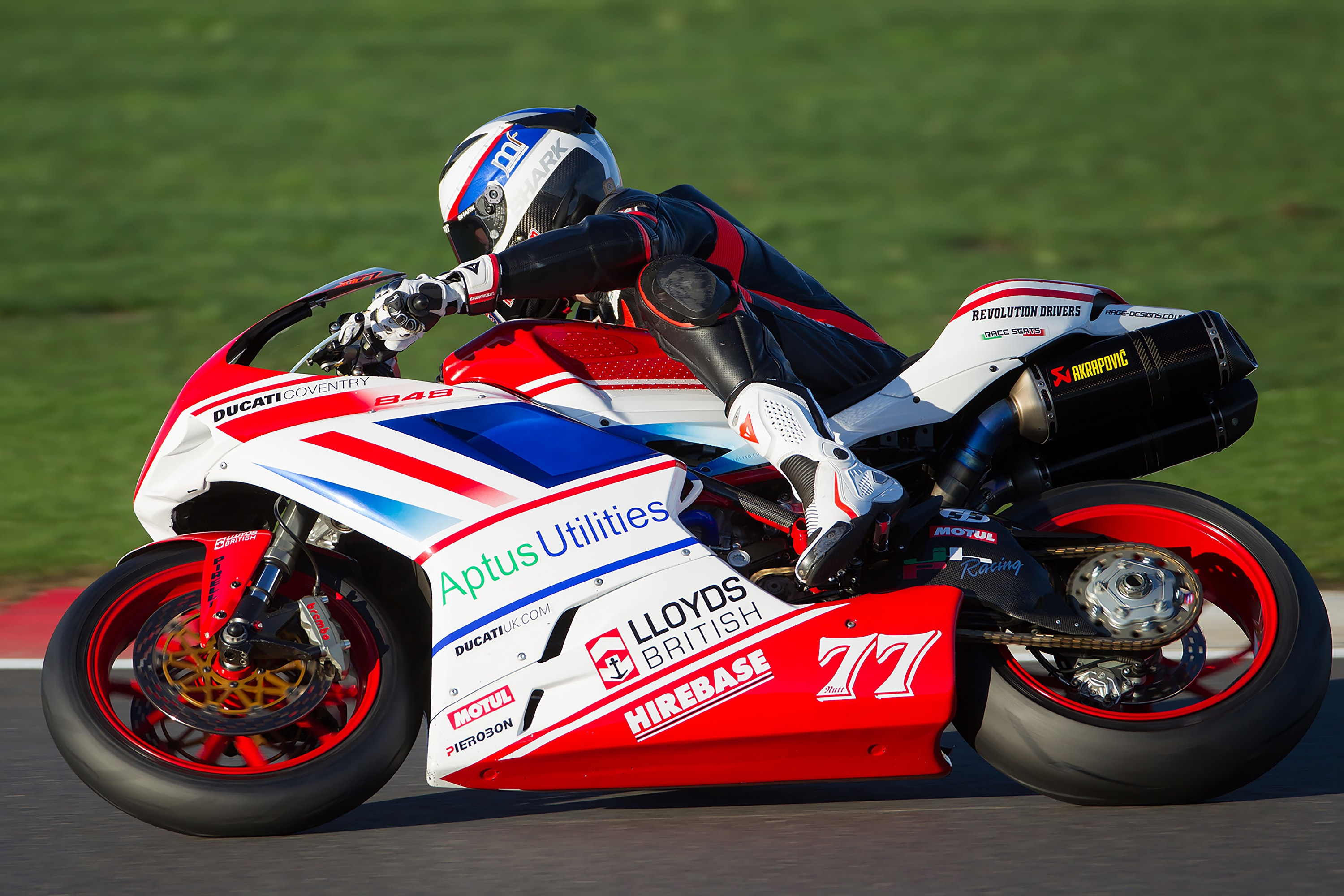 person riding red and white sportbike