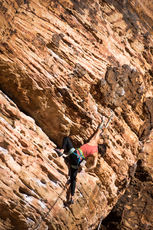 woman climbing rocky mountain