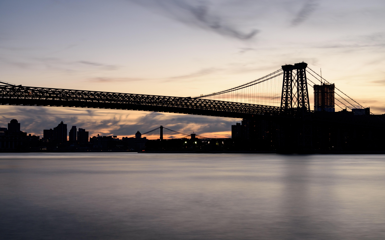 photo of bridge near body of water during night time