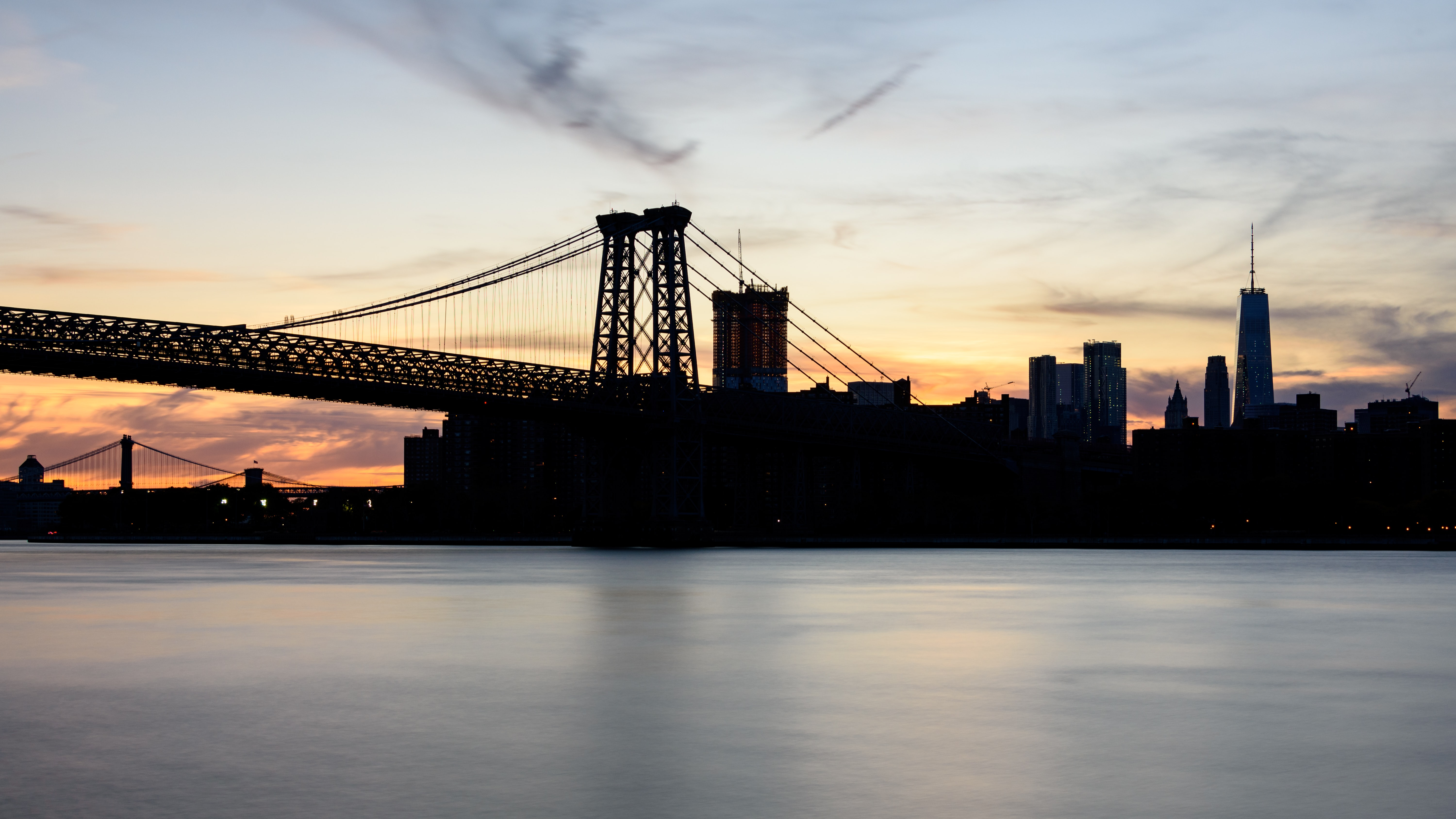 silhouette photograph of bridge and city buildings