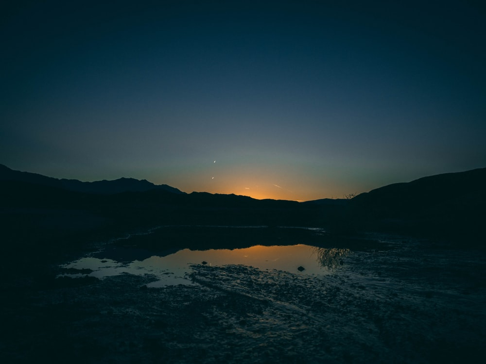 silhouette of mountain near body of water