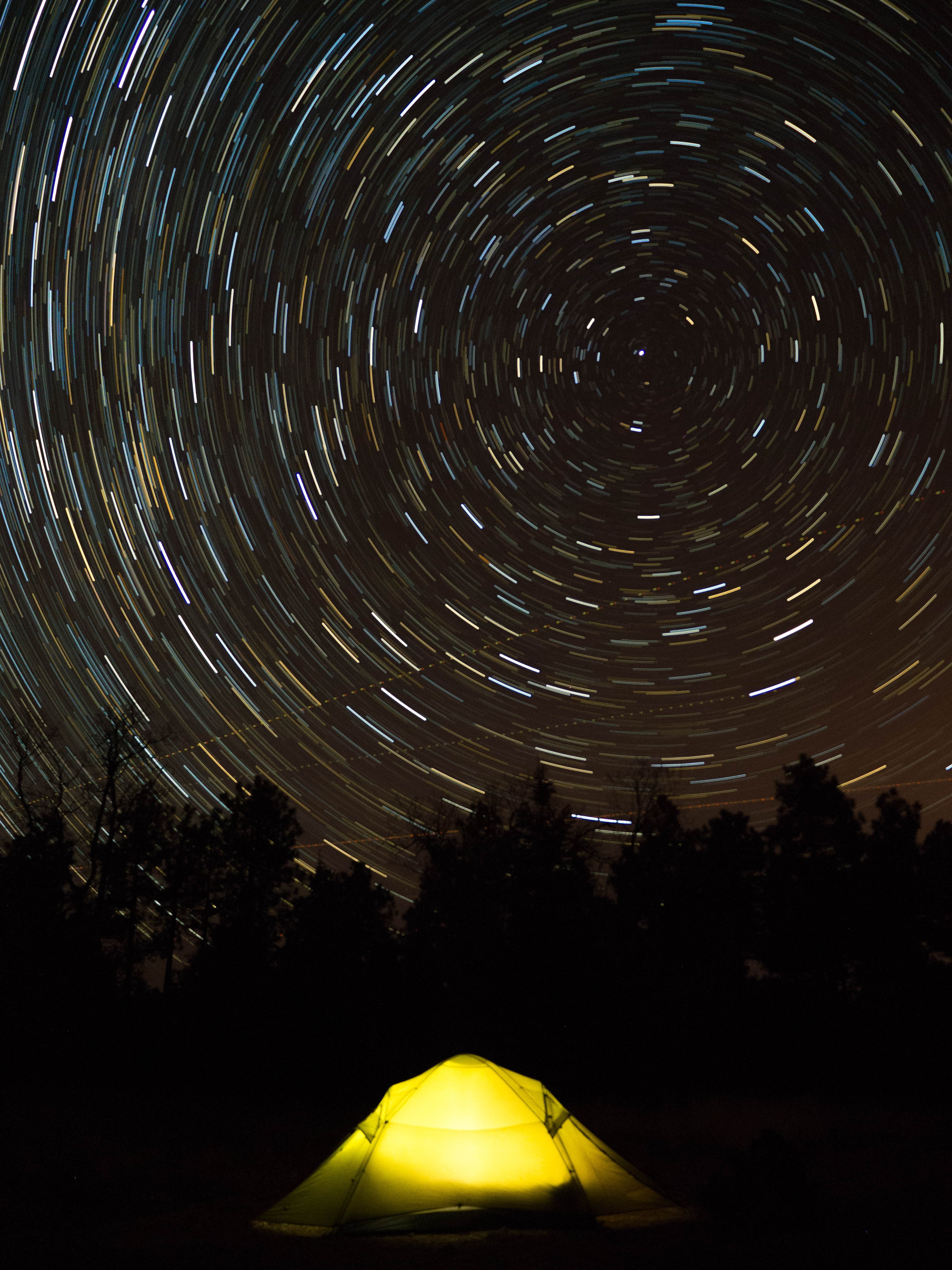 star trail photography of yellow camping tent