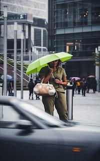 woman holding green umbrella walking in street
