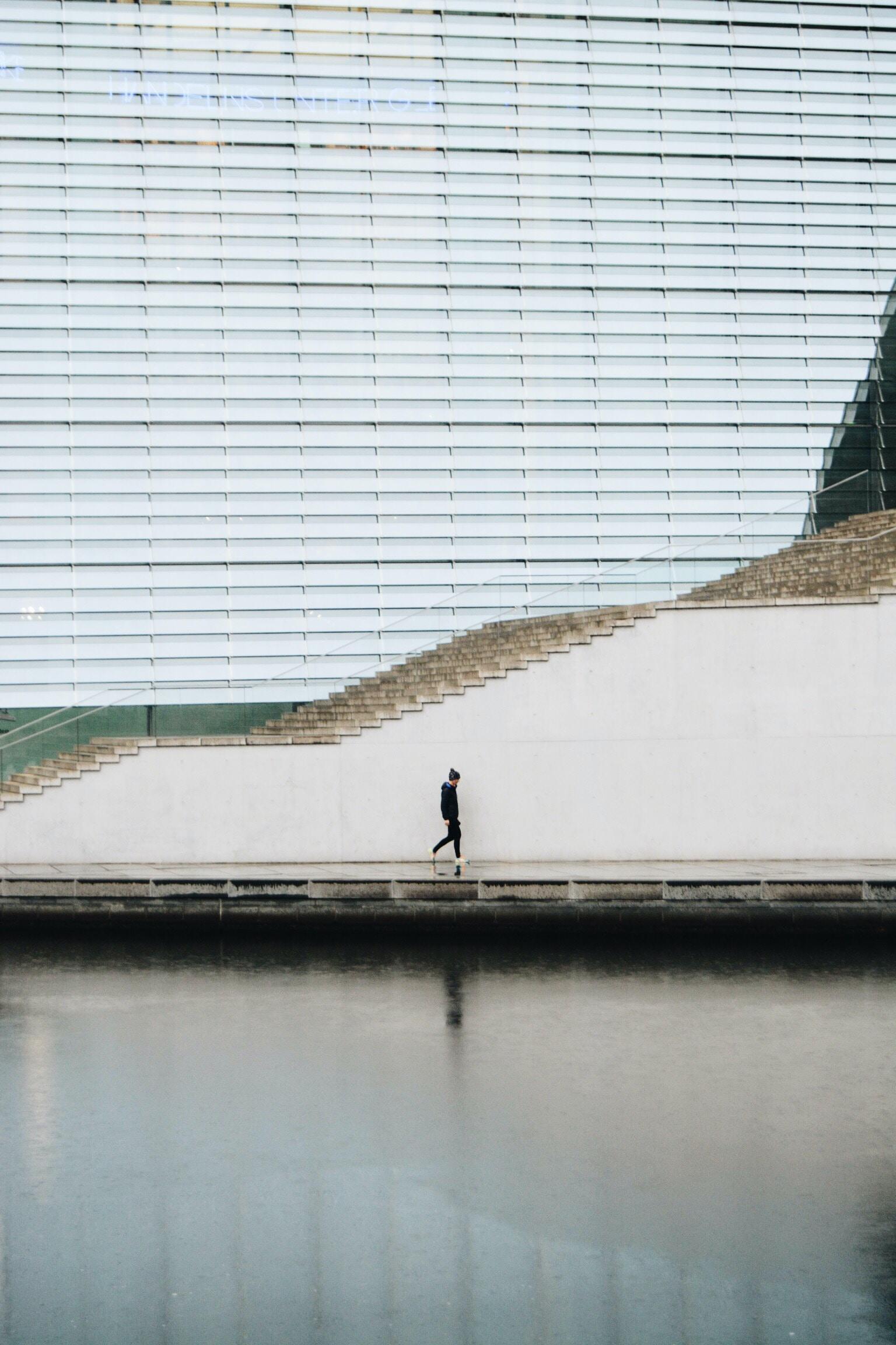 person walking beside concrete staircase