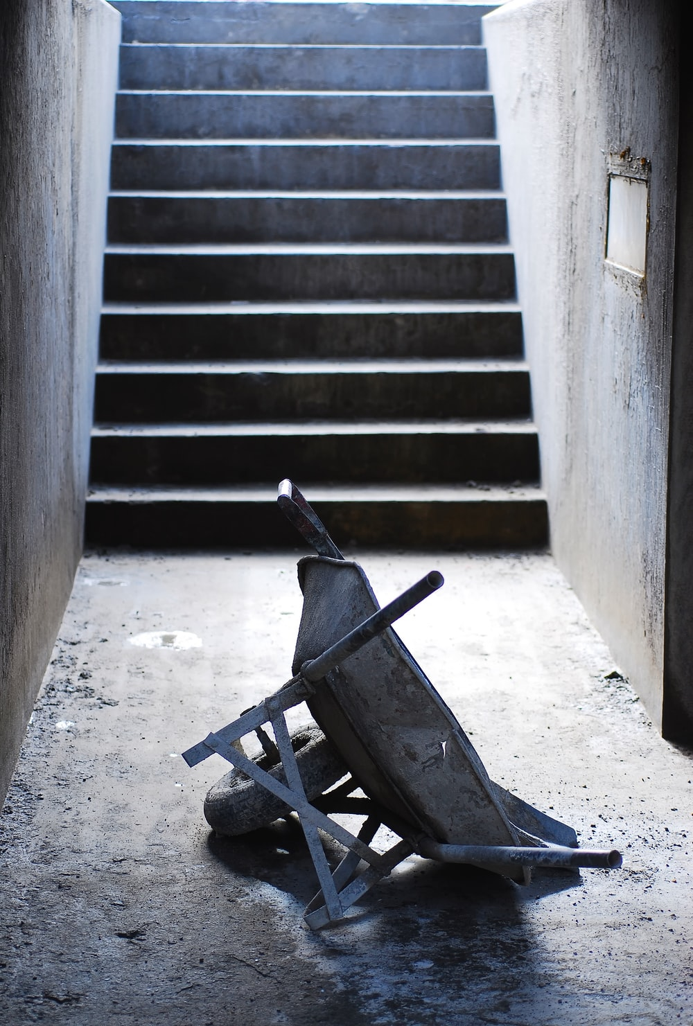 gray wheelbarrow near concrete steps