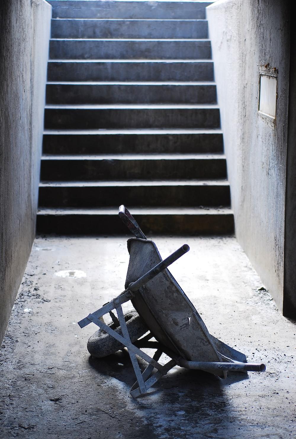 gray wheelbarrow near concrete steps