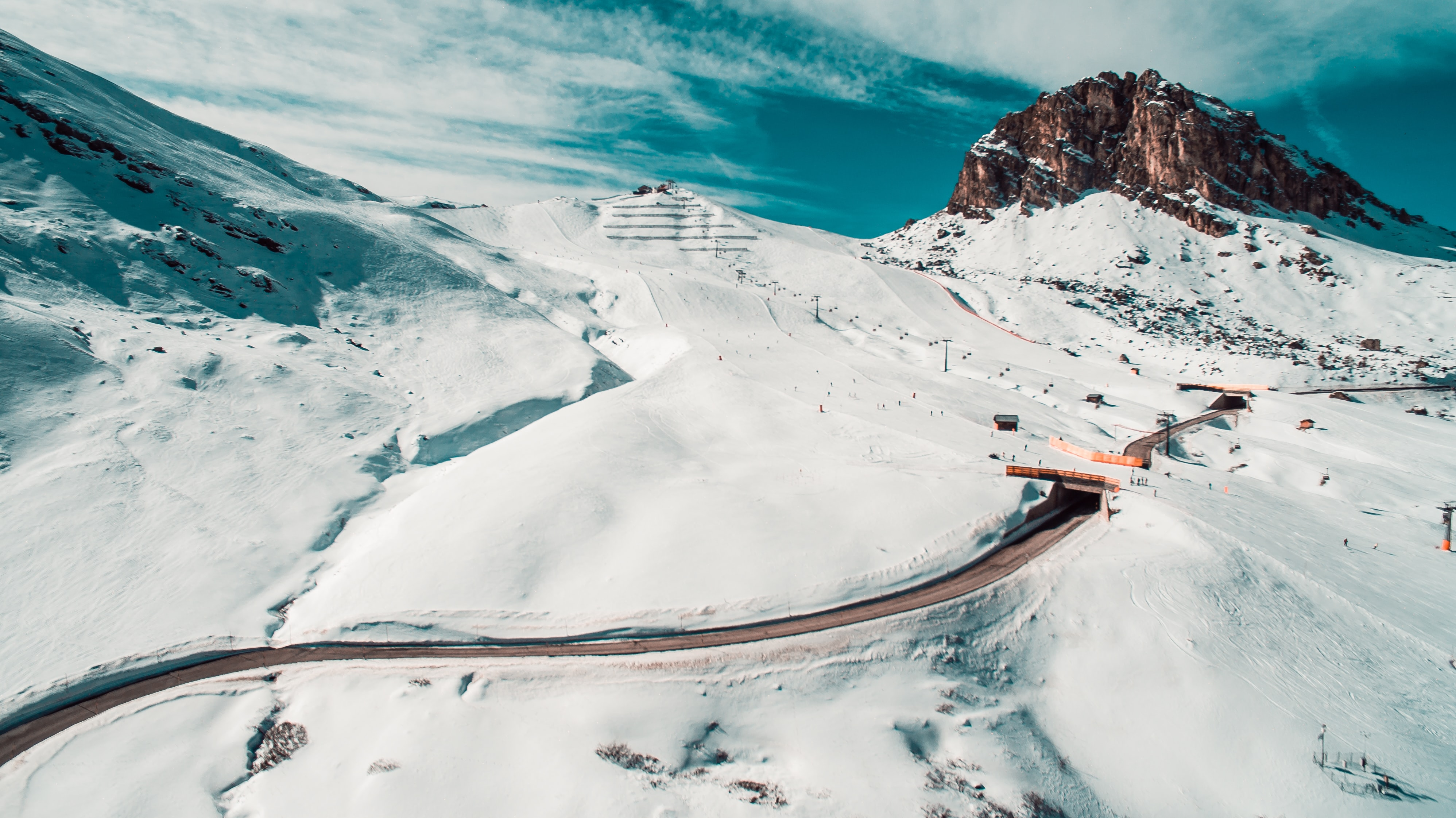 aerial view of road surrounded by mountain covered by snow