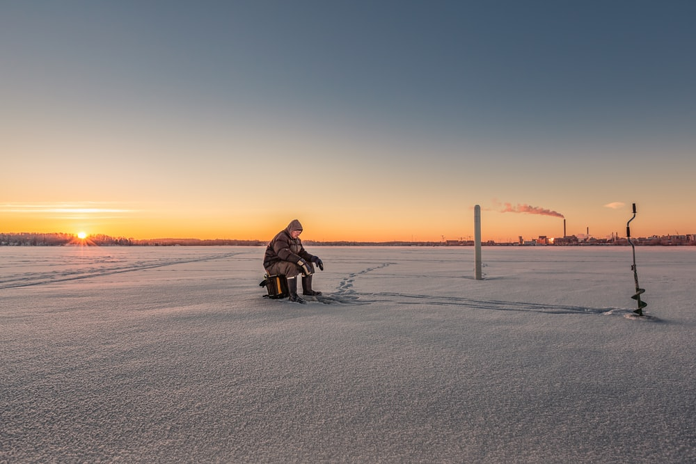 person sitting on stool on ice field near manual auger