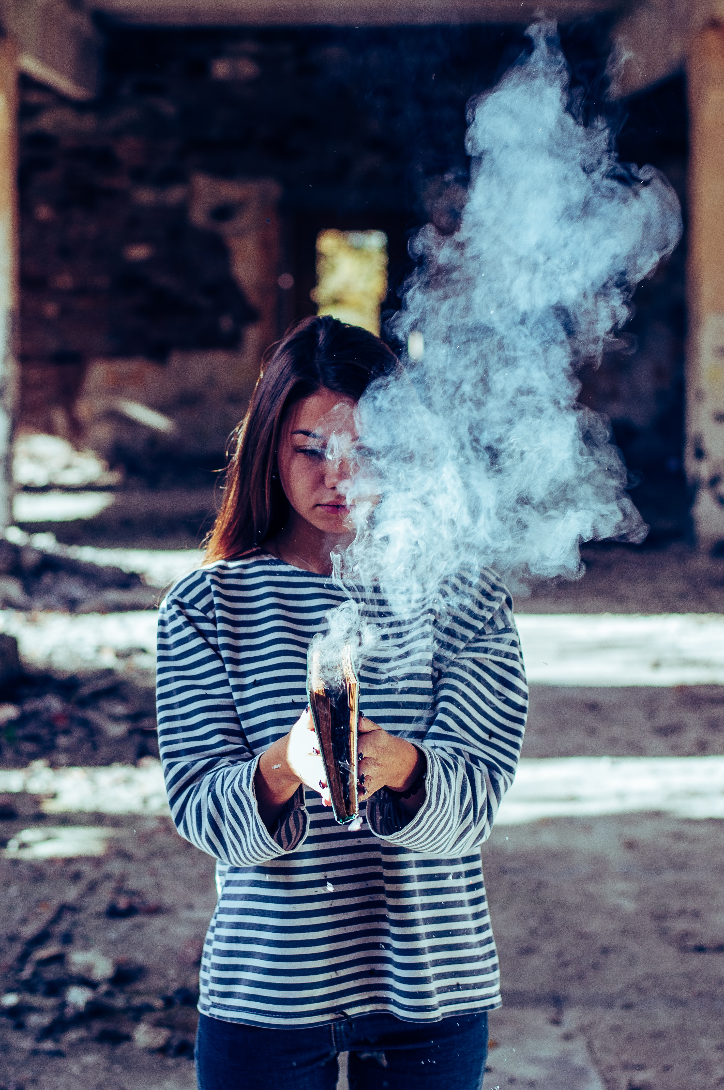 person holding book with smoke