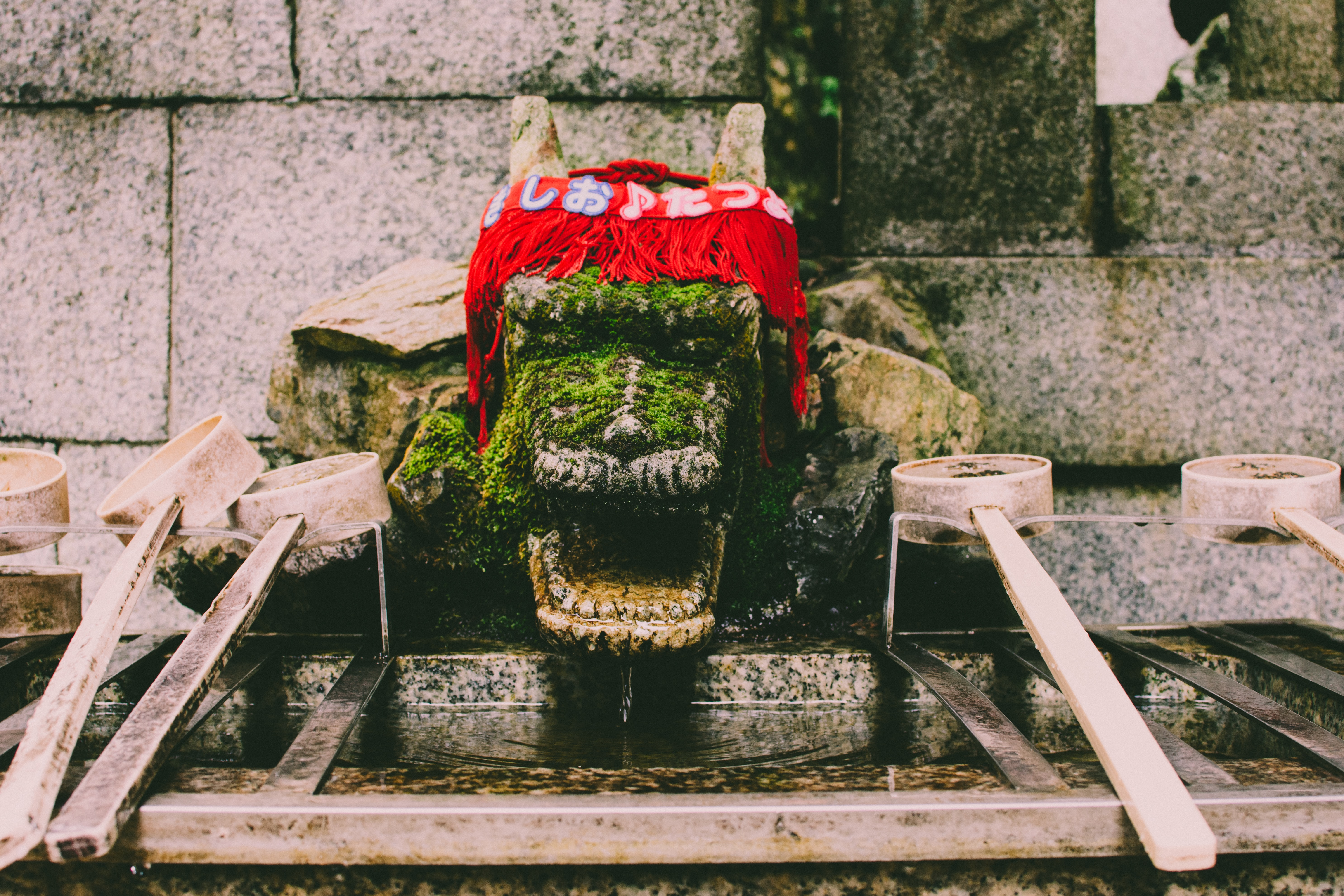 red knitted textile on top og green dragon statue