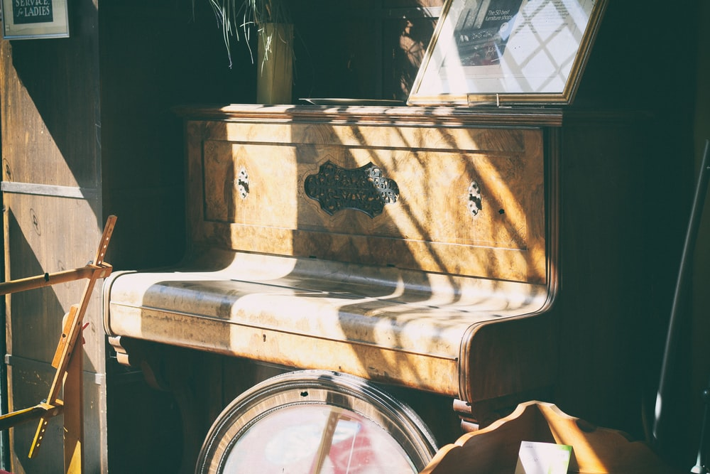 brown wooden upright piano inside the room at daytime