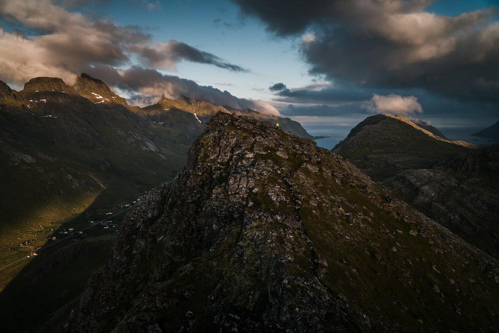 high angle photo of mountain range under cloudy sky