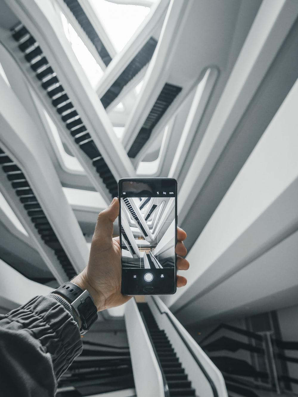 person taking a photo of escalators in building