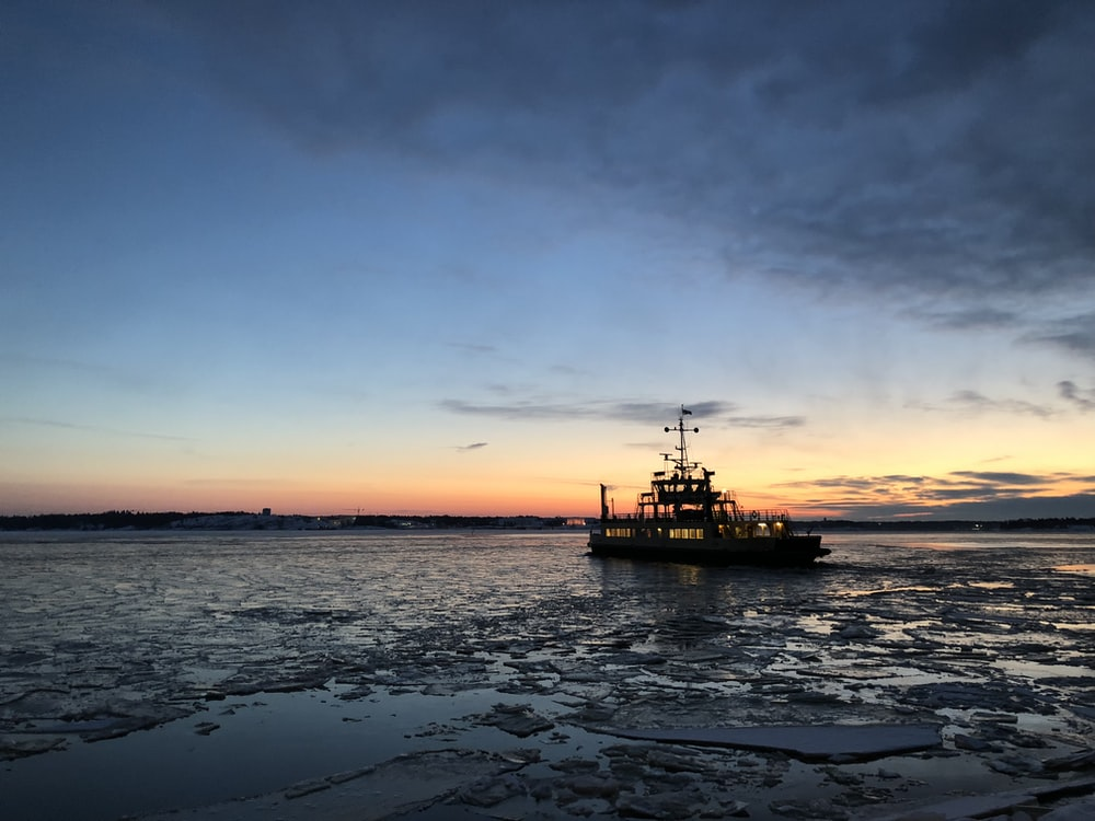 silhouette photo of a vessel on body of water
