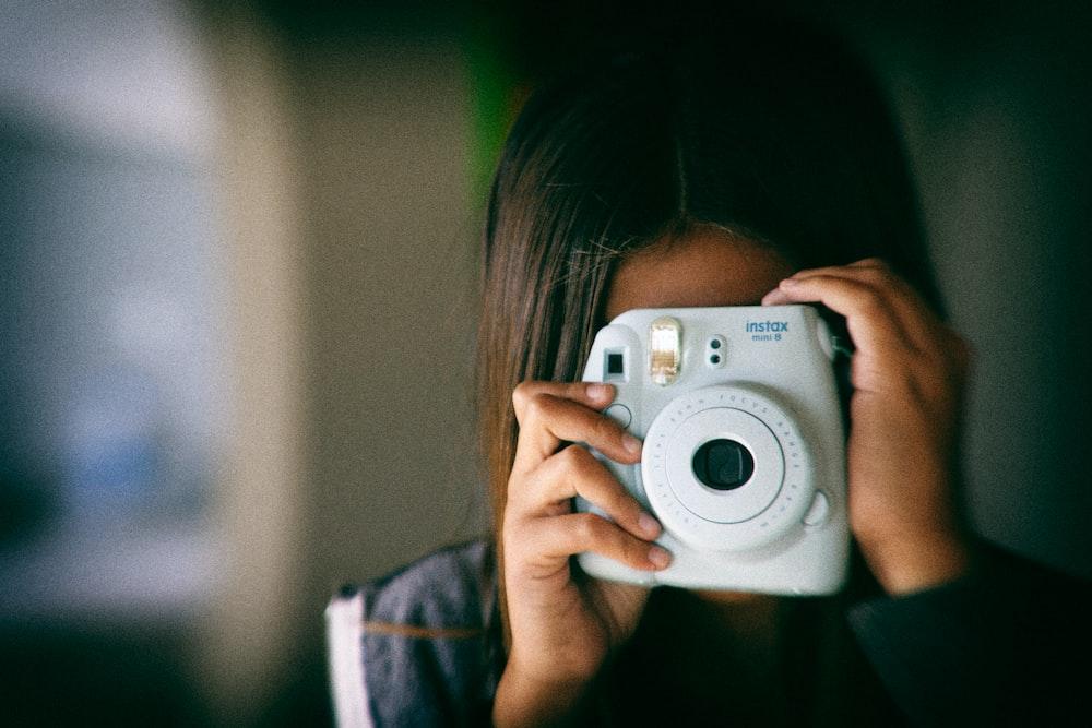 woman taking picture using white Fujifilm Instax Mini