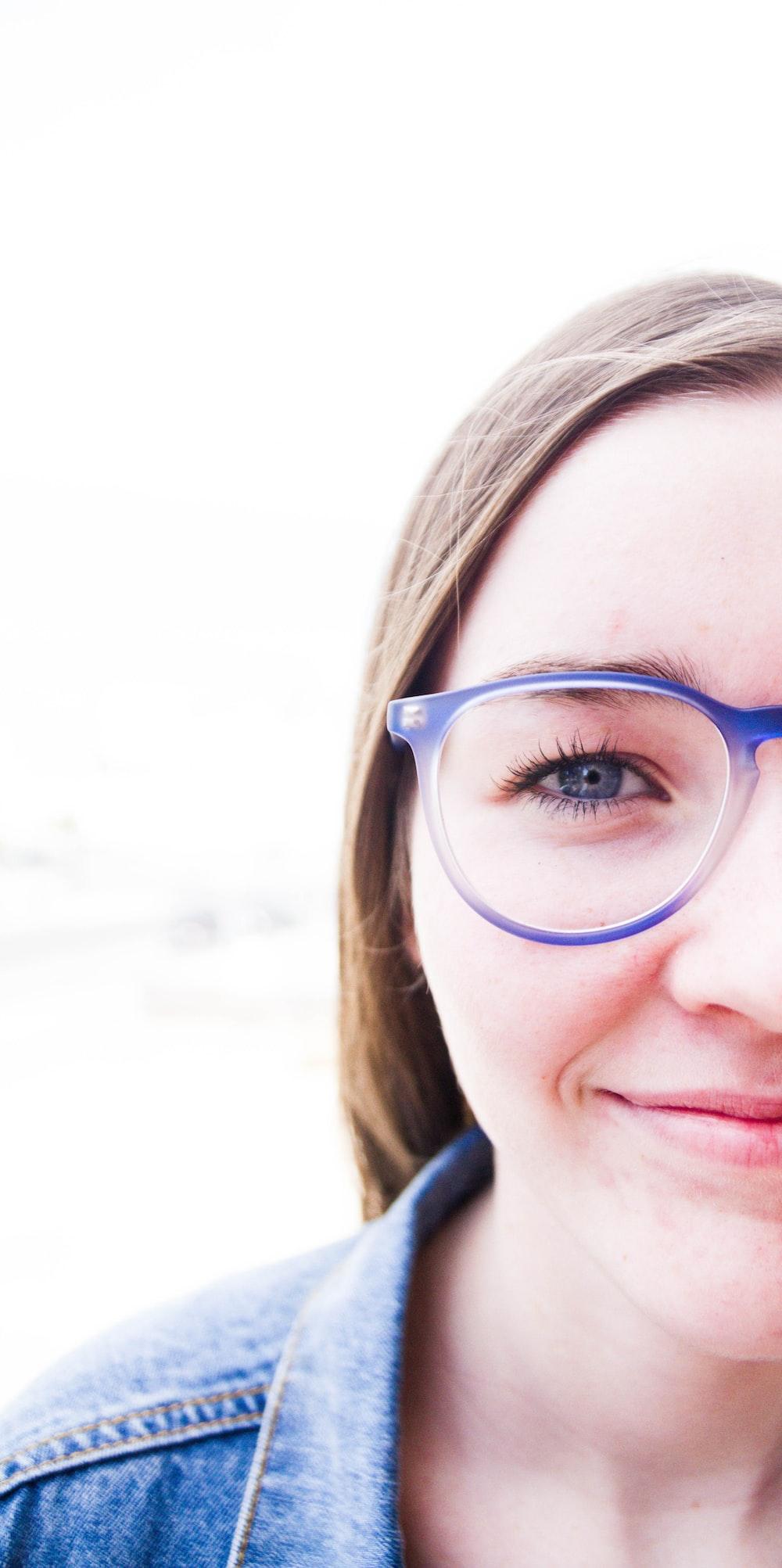 woman wearing blue framed eyeglasses and denim jacket